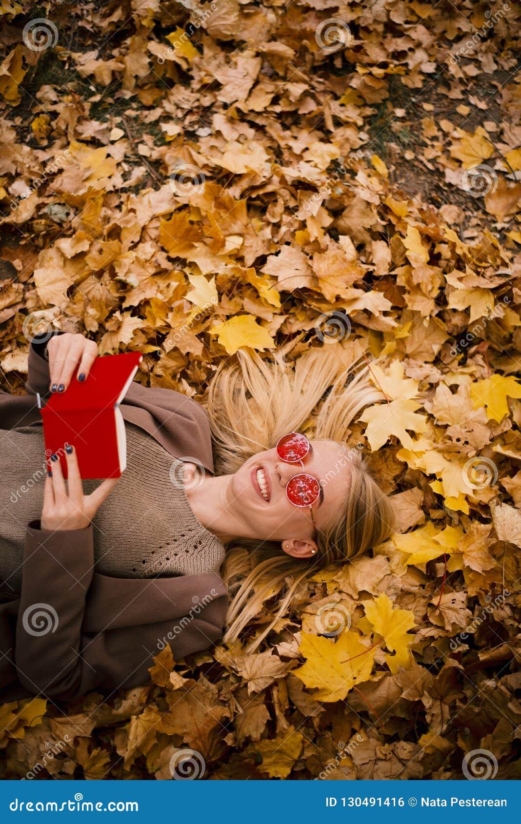 桃红色玻璃谎言的美丽的年轻金发碧眼的女人在黄色秋叶,读在红色盖子的一本书
