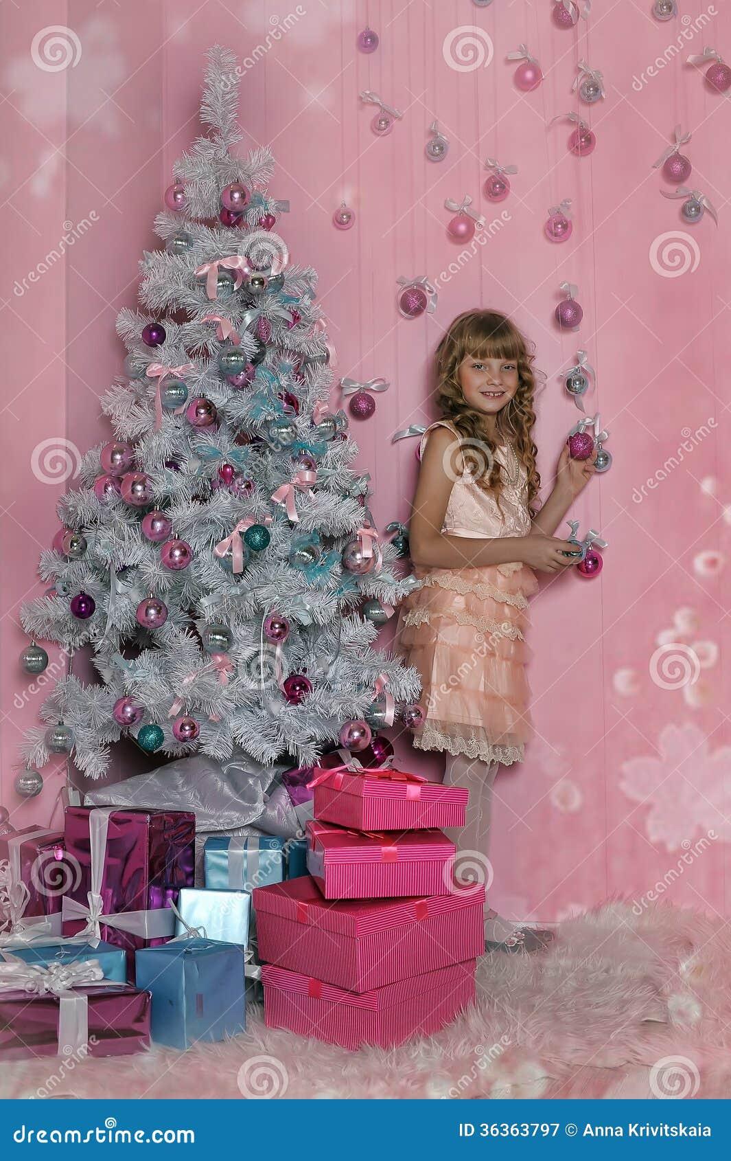 桃红色的女孩在圣诞树