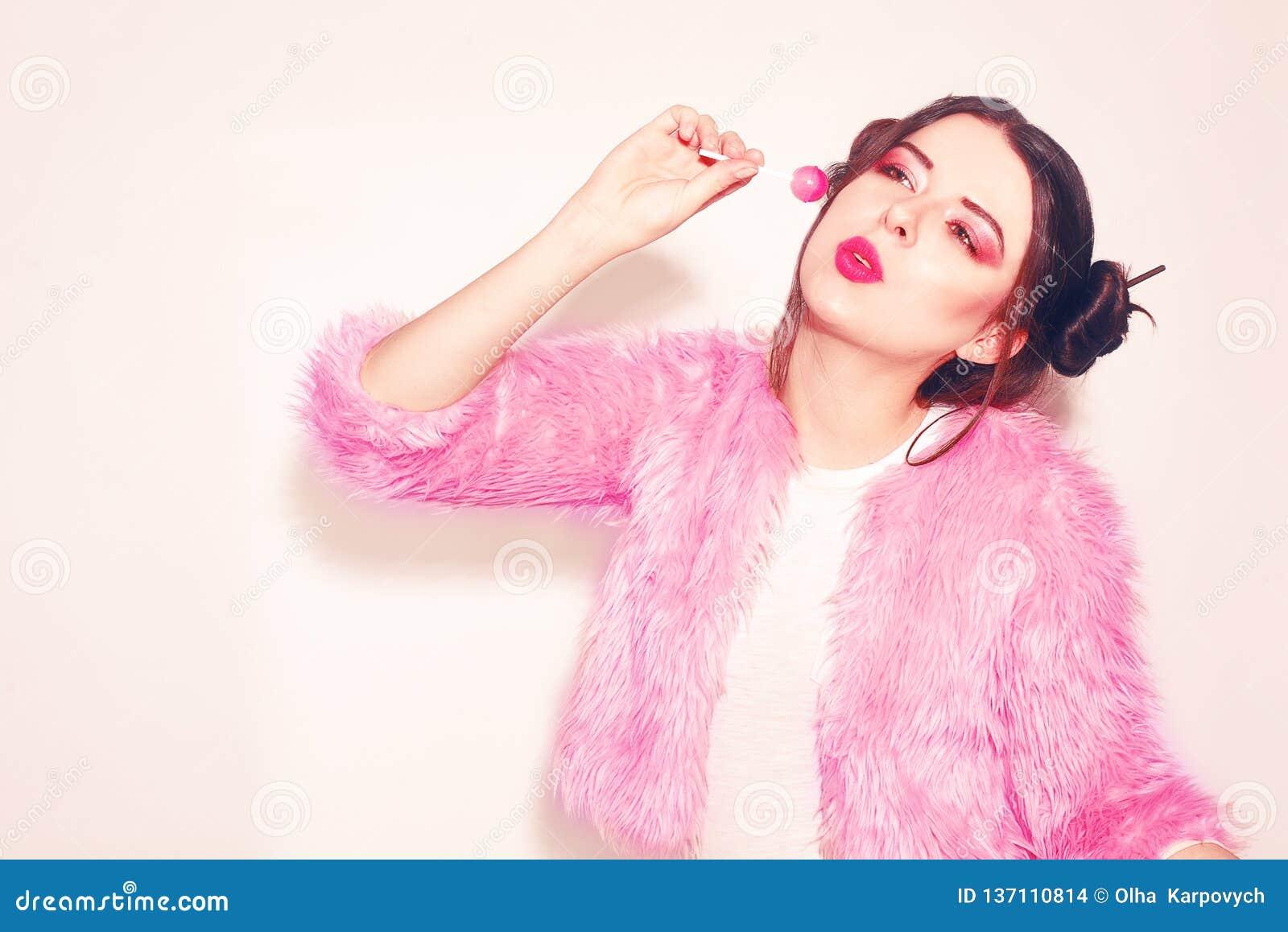 桃红色的女孩用胜利小圆面包吃珍宝珠 吃在桃红色背景的一俏丽的少女的画象棒棒糖