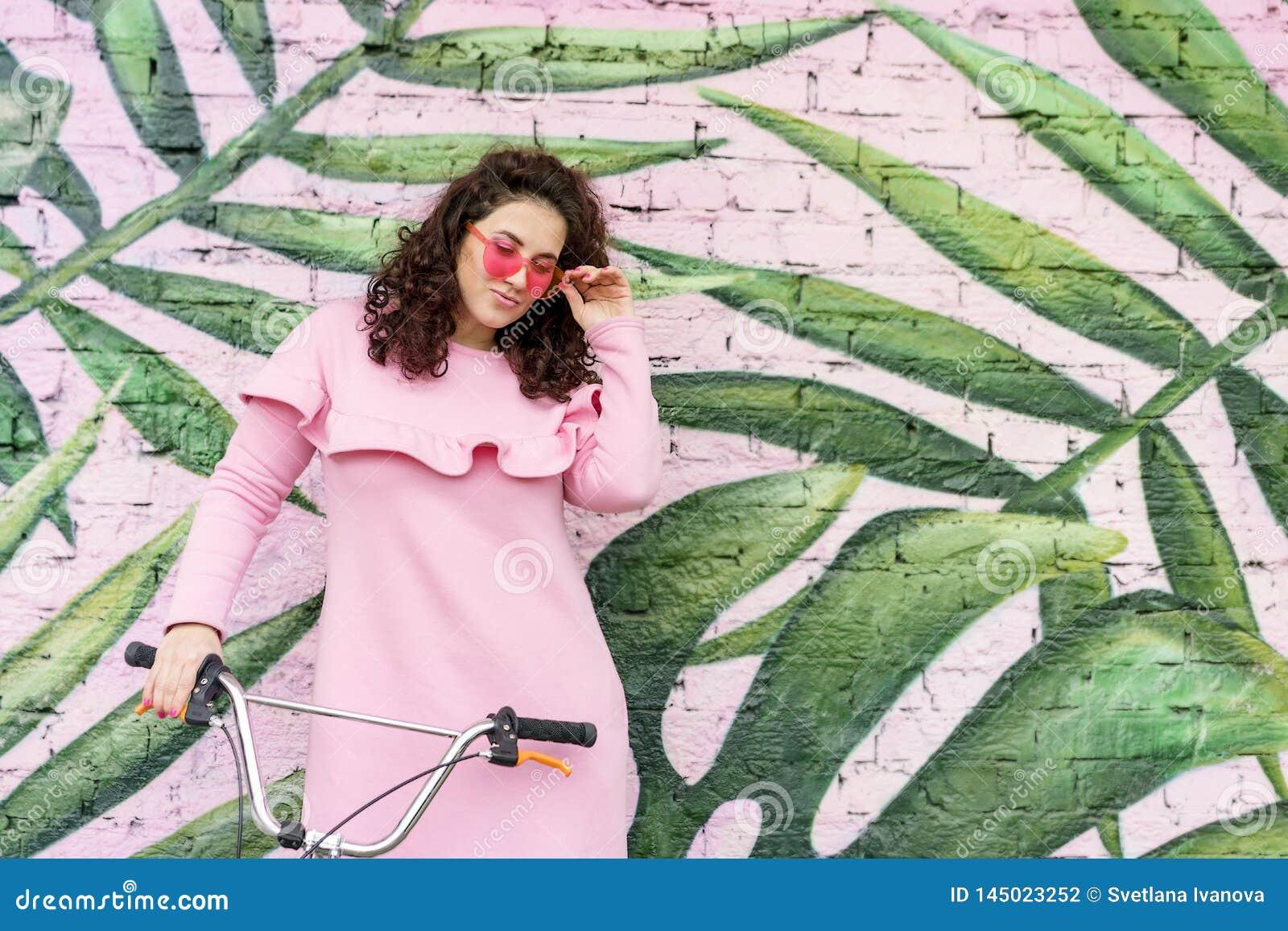 桃红色礼服和桃红色玻璃的长发卷曲深色的妇女
