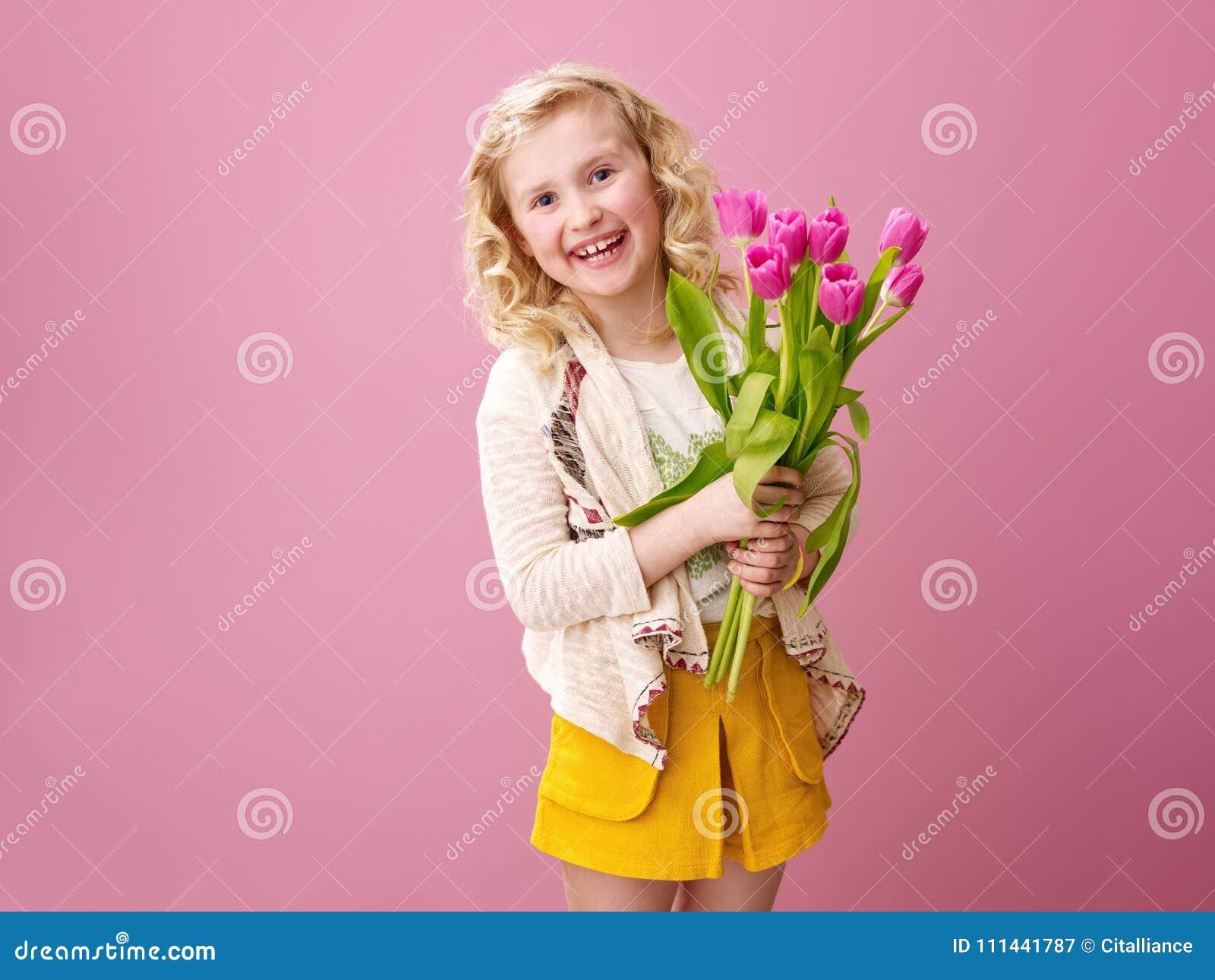 桃红色背景的微笑的现代女孩与花花束