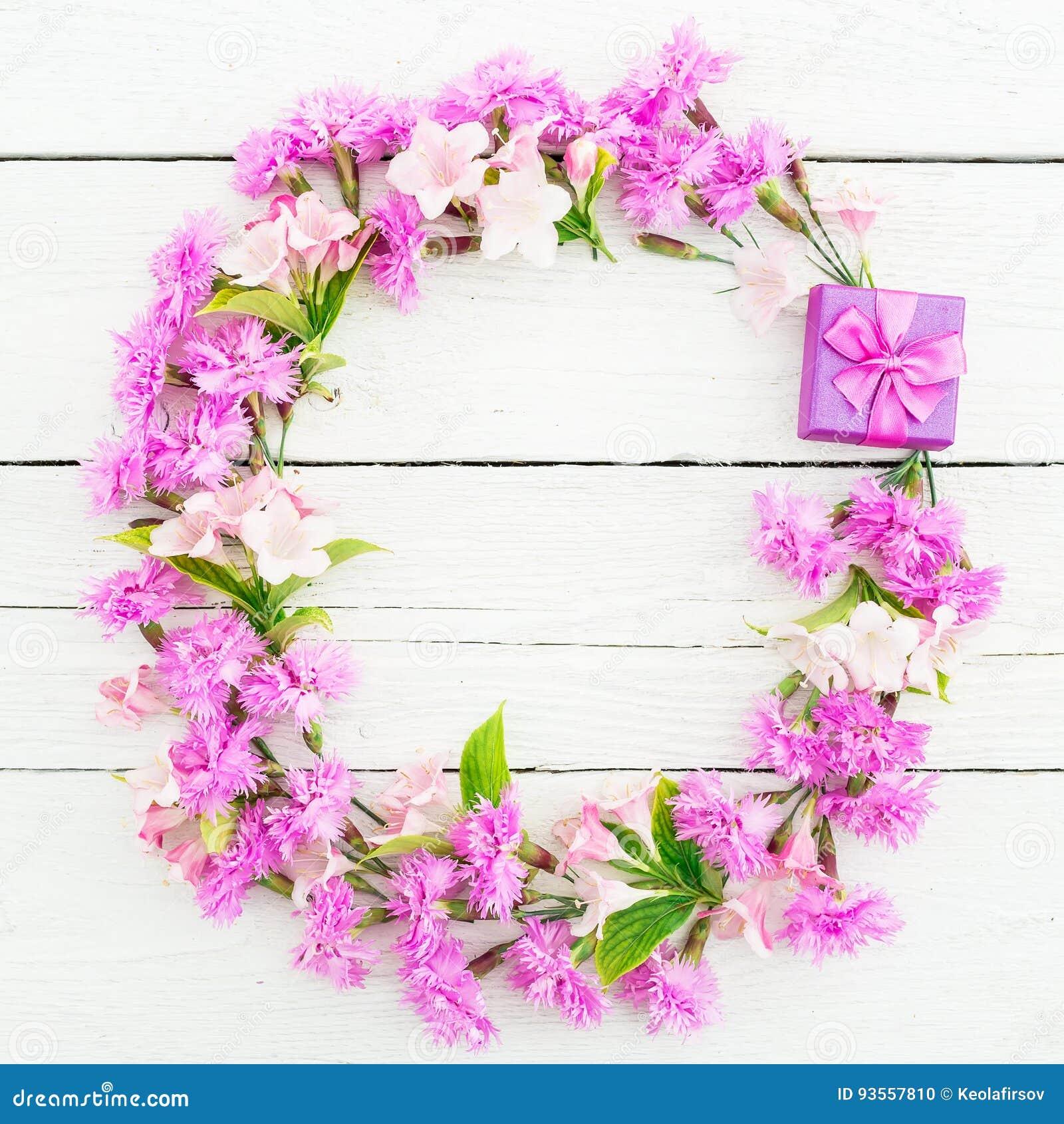 桃红色花和圆环箱子的花卉样式在白色土气背景 平的位置,顶视图 花卉框架概念