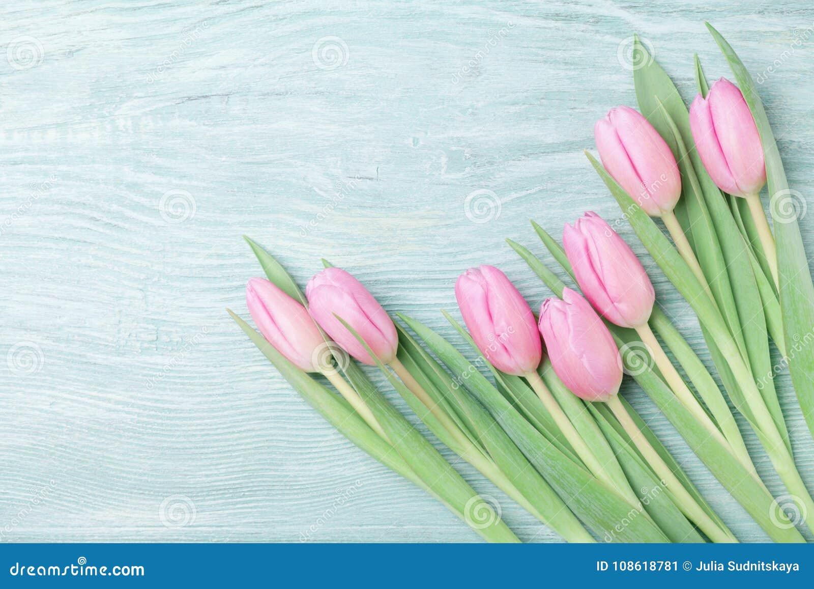 桃红色郁金香在土气桌上开花为3月8日,国际妇女或母亲节 美好的看板卡春天 顶视图
