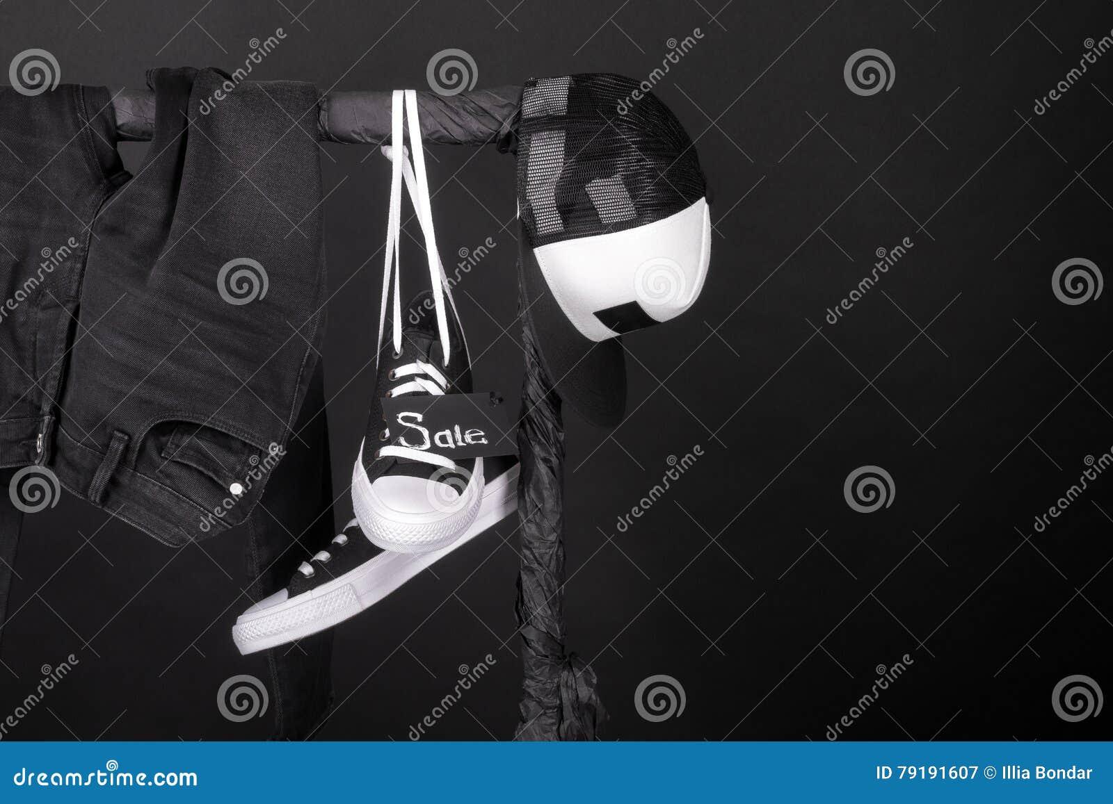 桃红色销售额黄色 黑白运动鞋,盖帽气喘,垂悬在衣裳的牛仔裤折磨背景 星期五 复制空间