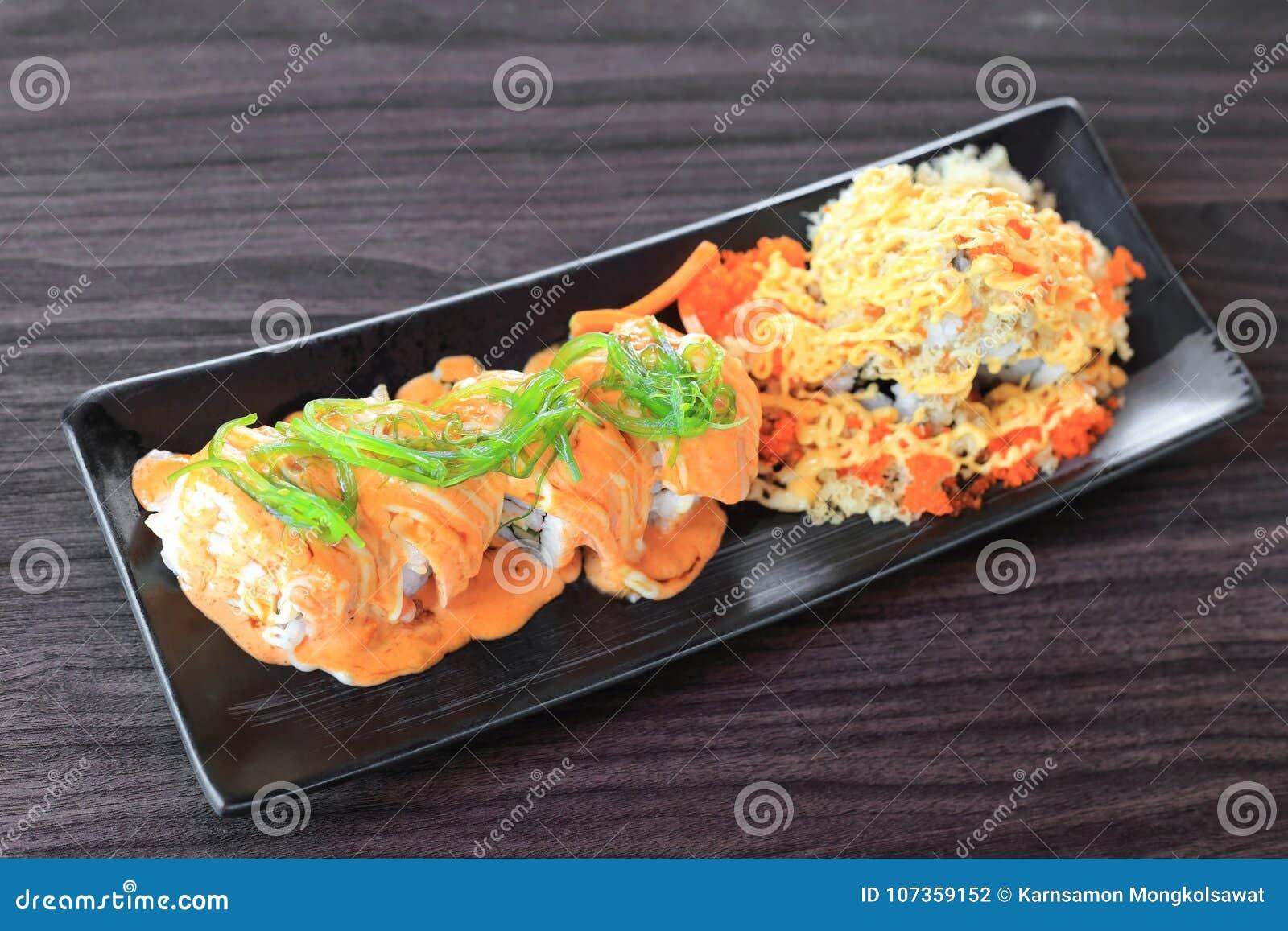梅基寿司卷由与wakame海草的三文鱼上面制成和特别寿司冠上用酥脆天麸罗面粉、蛋黄酱和飞鱼