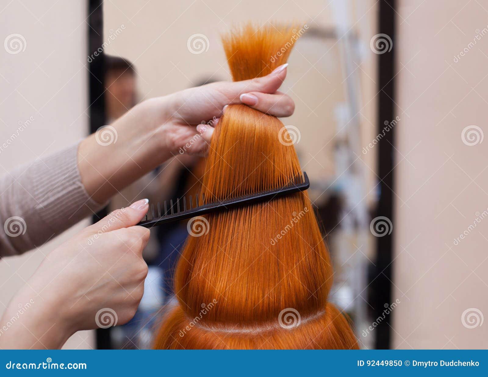 梳她他的客户的长,红色头发的美发师