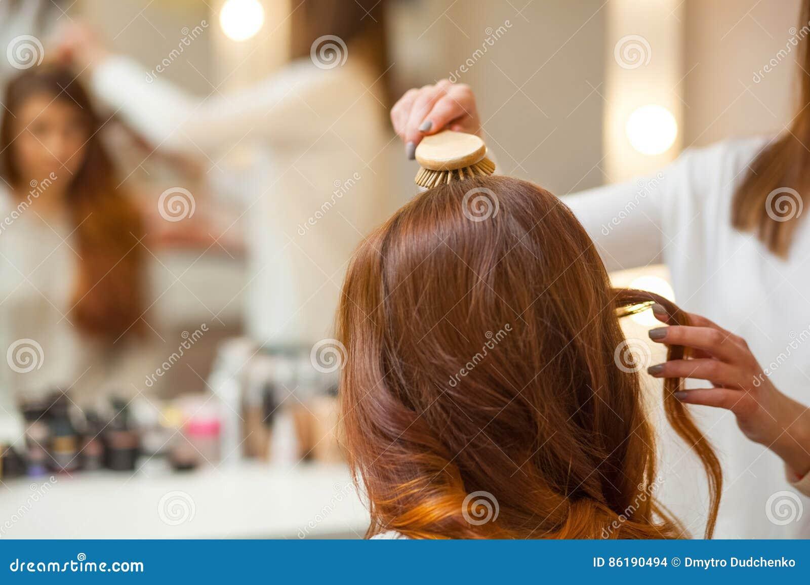 梳她他的美容院的客户的长,红色头发的美发师
