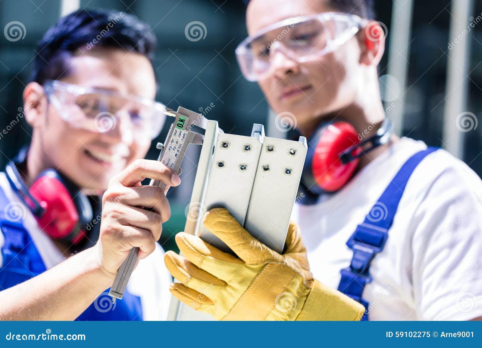 检查工作片断的亚裔工作者在生产设备