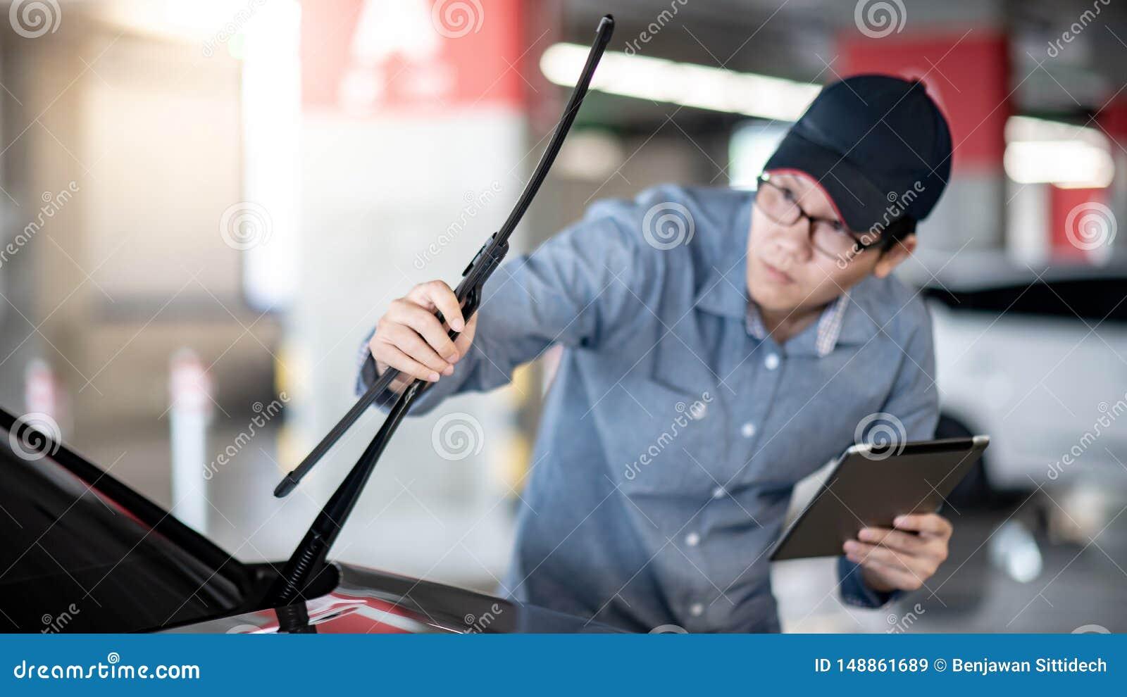检查风档刮水器的亚裔汽车机械师