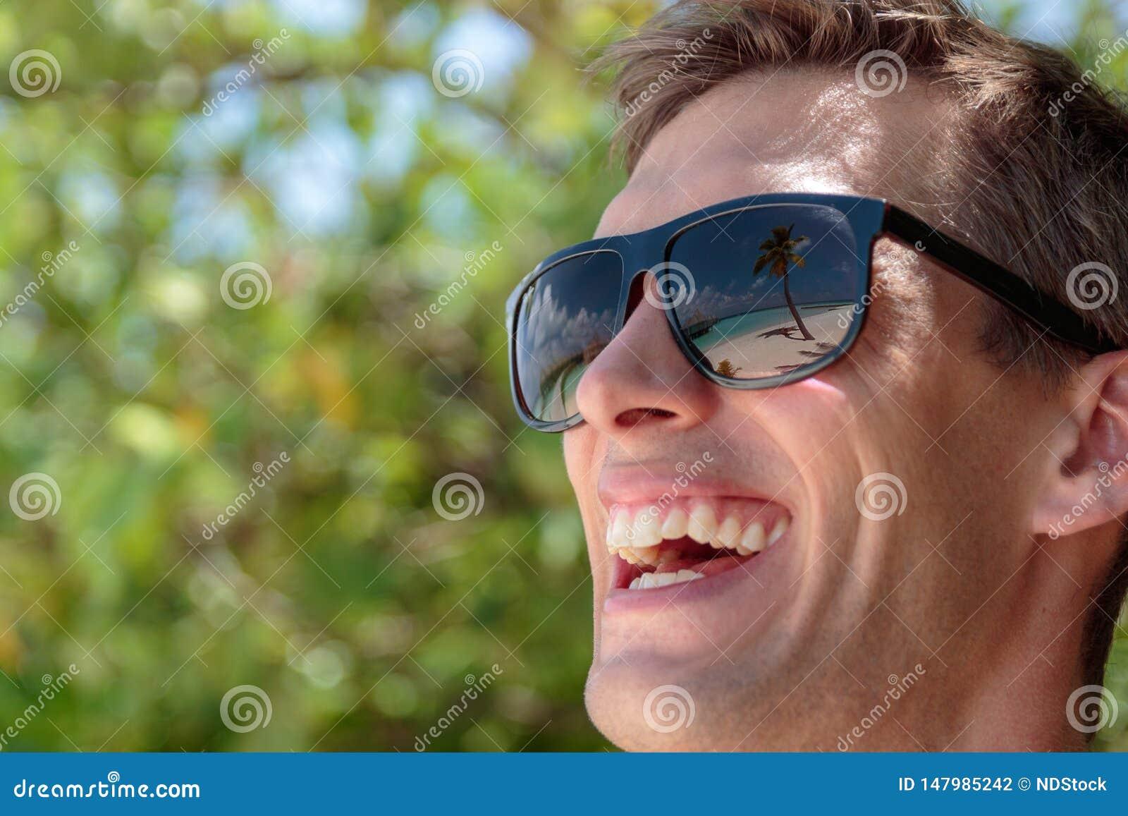 棕榈树、白色在一个愉快的人的太阳镜反映的海滩和透明的大海 r