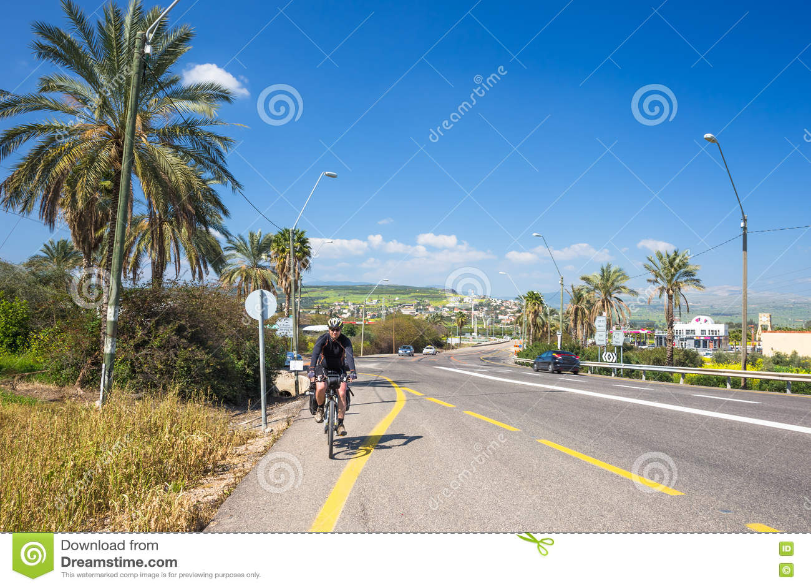 棕榈背景的愉快的骑自行车的人在以色列