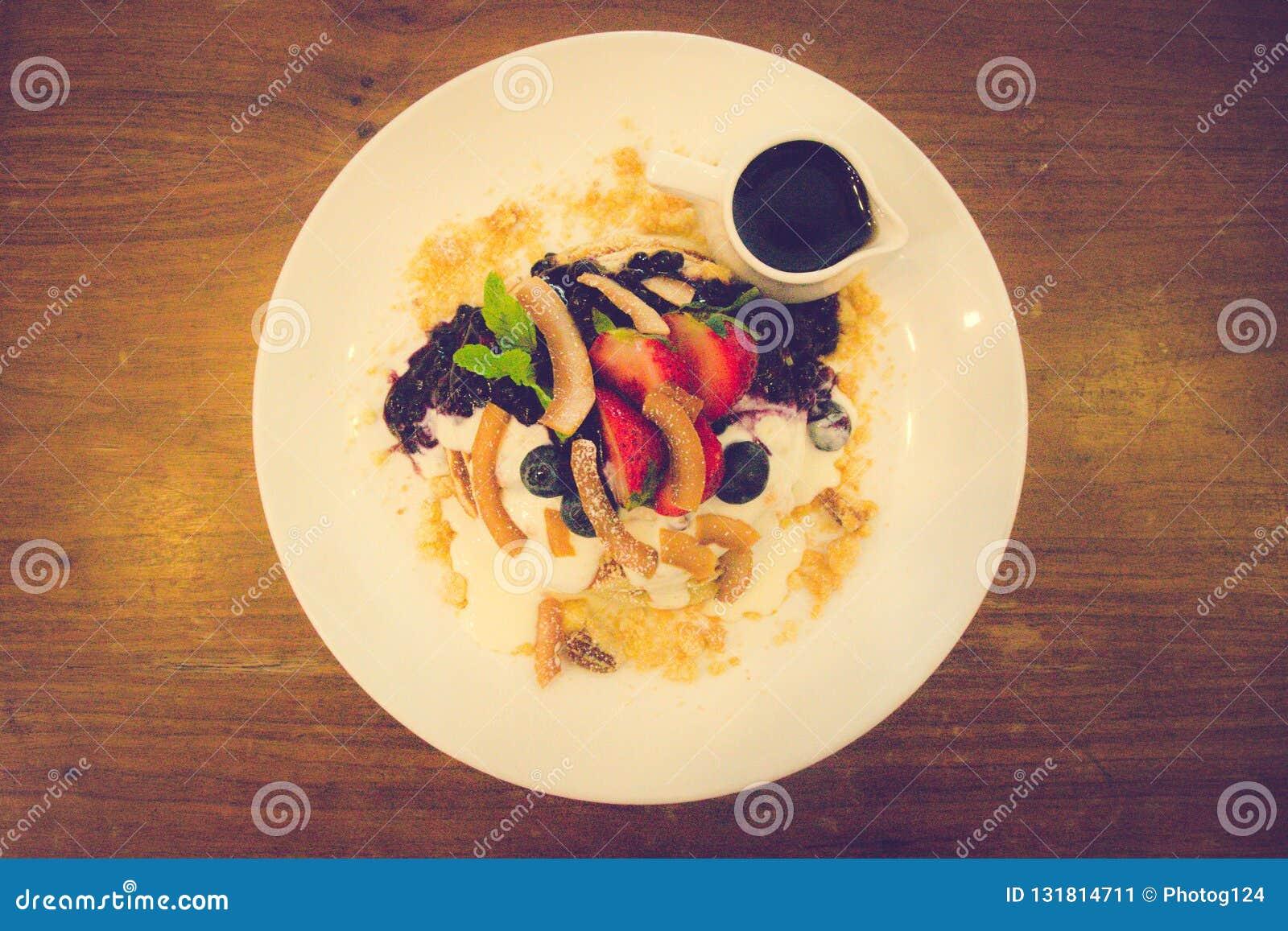 椰子面粉薄煎饼蓝莓蜜饯,新鲜的香蕉鞭打了希腊酸奶