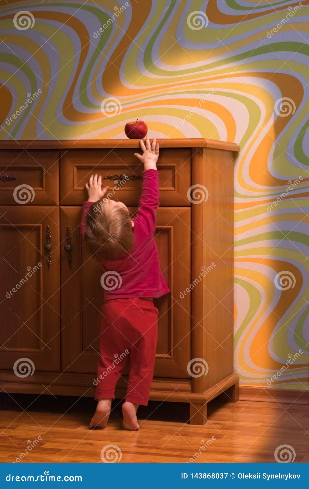 概念性的坚持 婴孩营养概念 设法的小孩到达红色苹果 孩子的愉快的膳食 新鲜水果