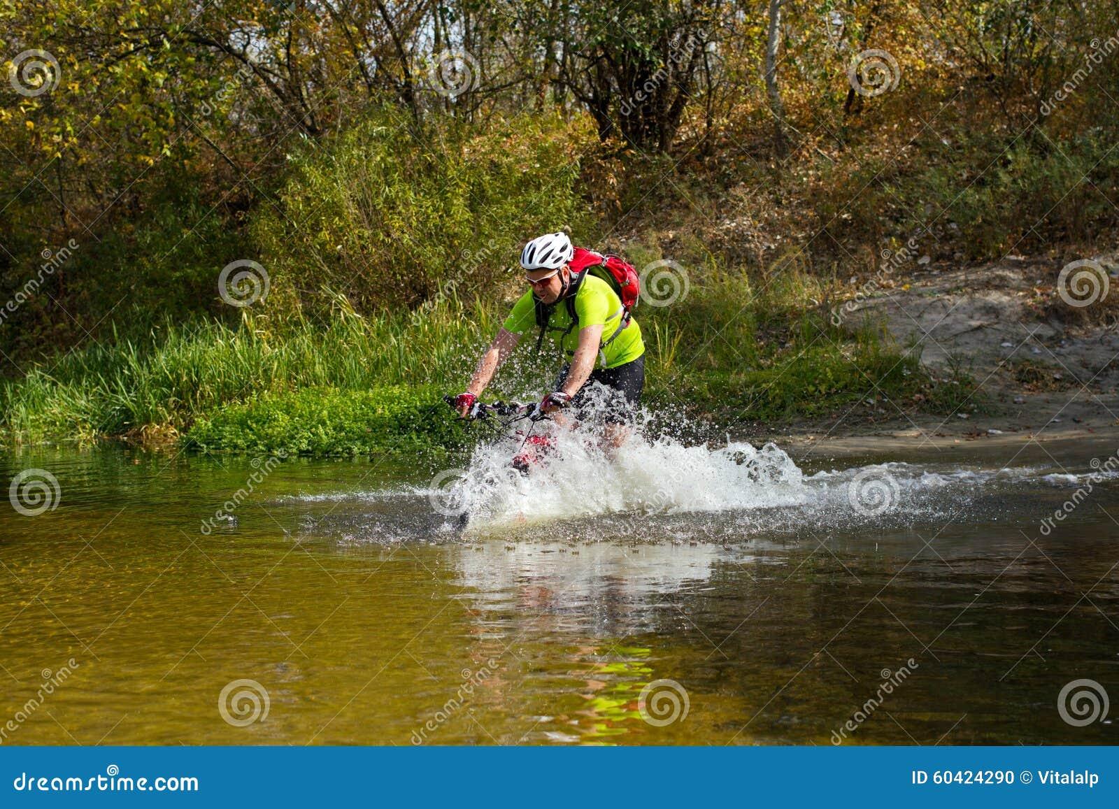 横渡有自行车的年轻运动员岩石地形在他的手上