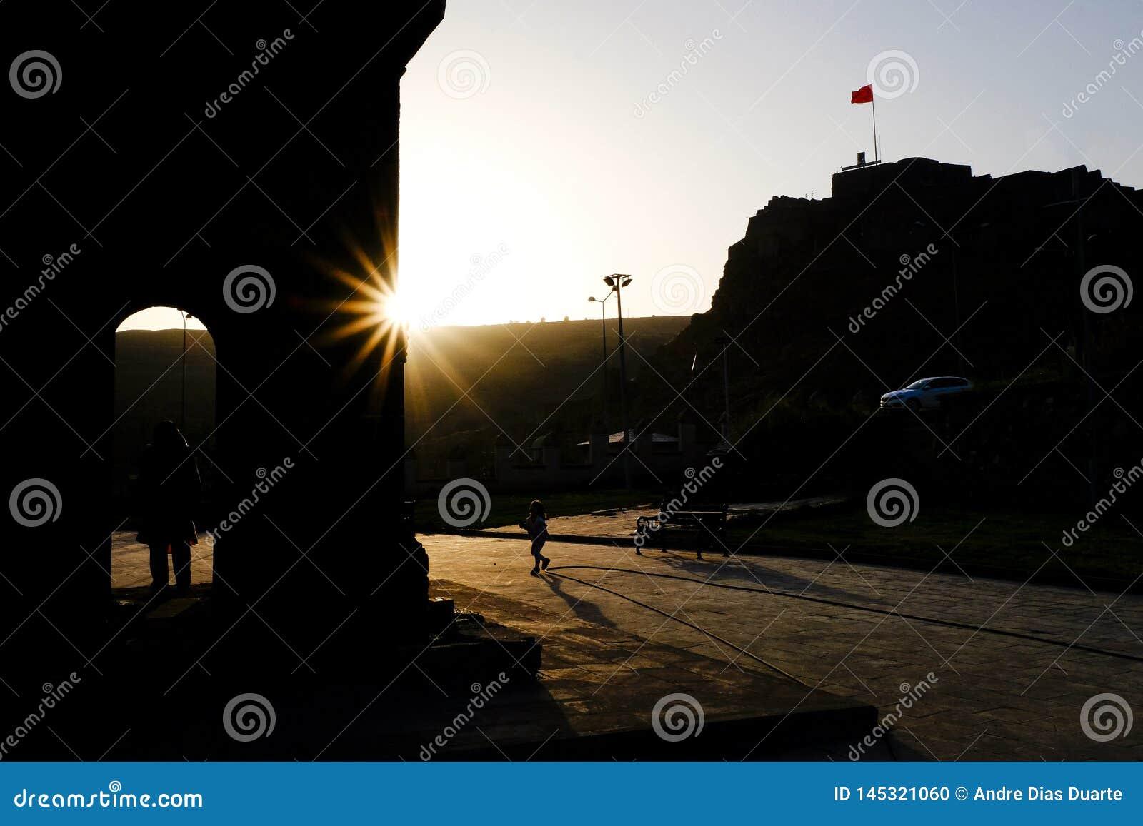 横跨正方形的儿童赛跑在反对光的日落