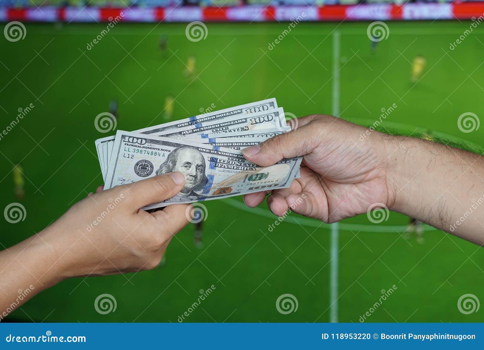 橄榄球赌博的概念:手给别的捐钱在电视