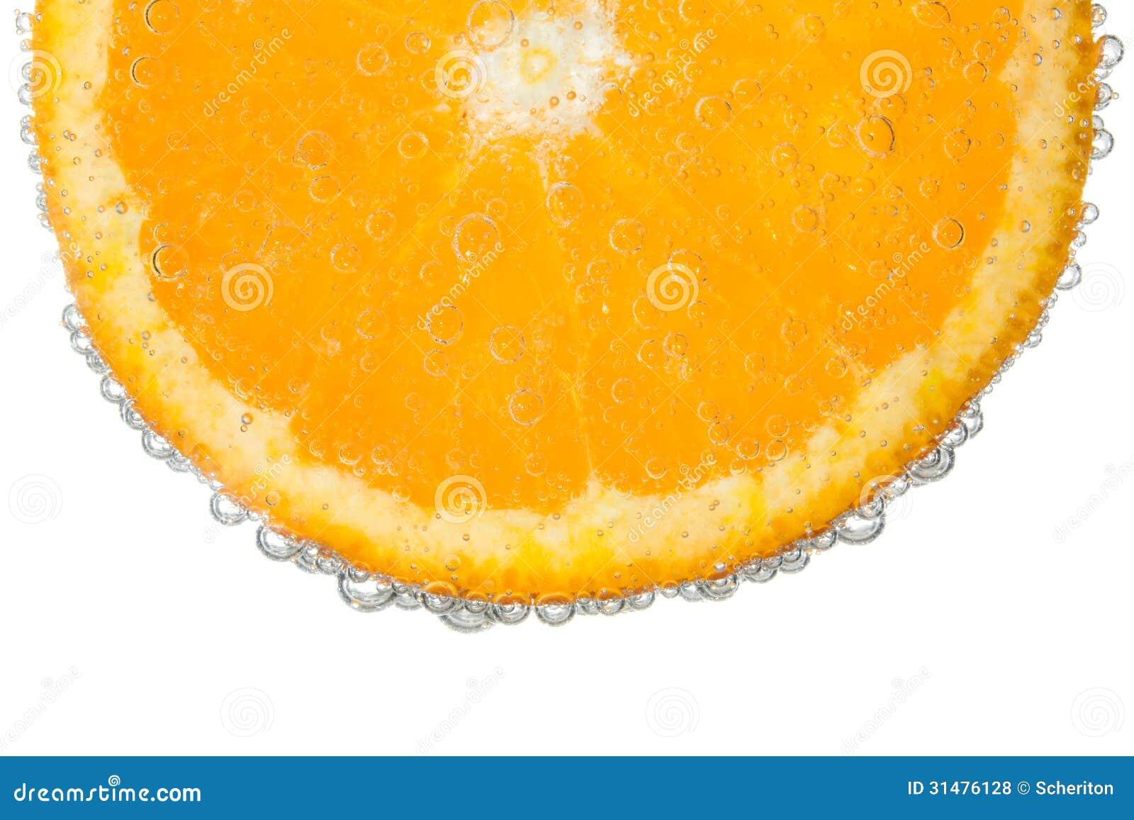 橙色切片在清楚的泡沫腾涌的水泡影背景中