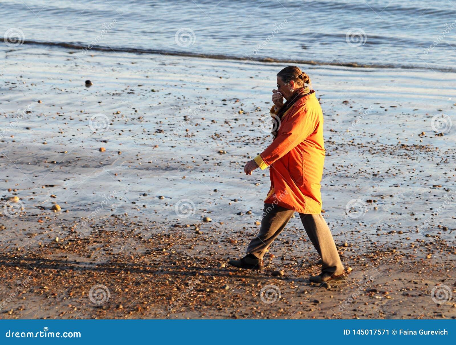 橙色外套的一名妇女走在海滩的在早期的春天在格洛斯特,马萨诸塞