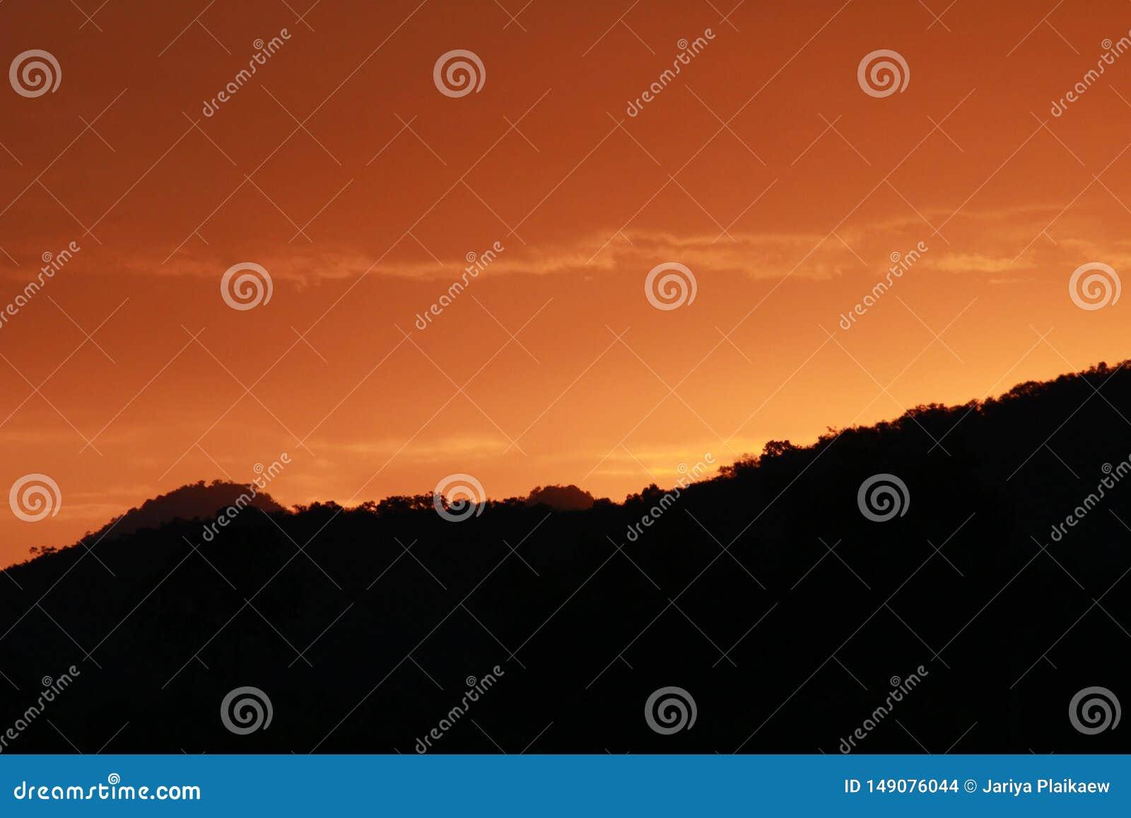 橙色天空和黑暗的山
