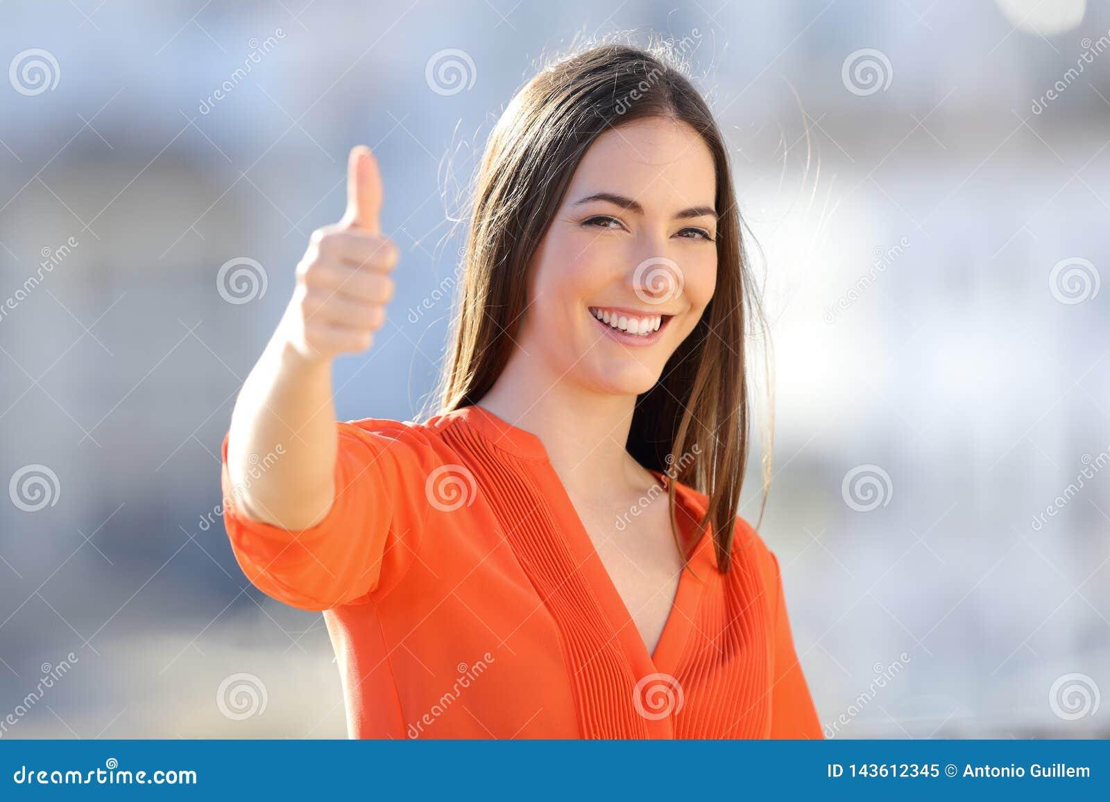 橙色打手势的赞许的愉快的妇女在镇