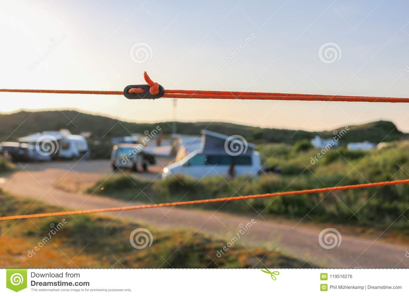 橙色拿着帐篷的定绳和黑调整器平稳在它的地方