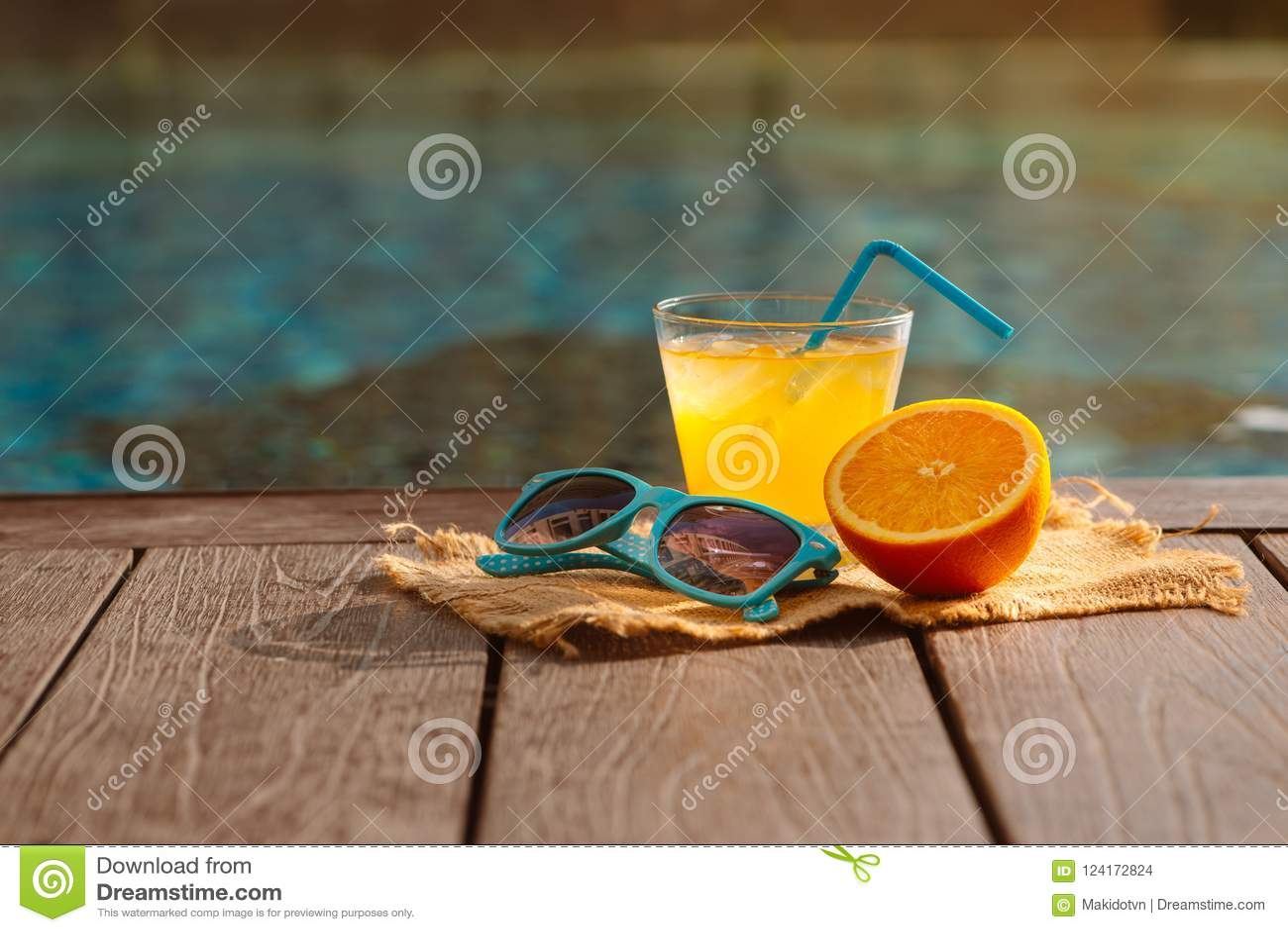 橙色新汁液圆滑的人饮料,太阳镜临近游泳池