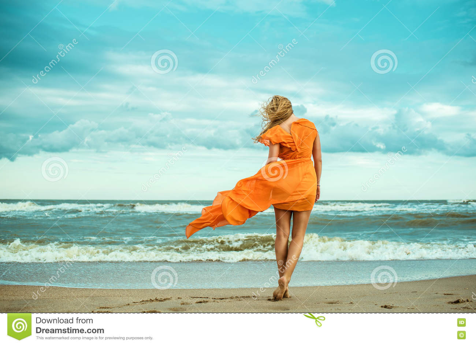 橙色礼服的一名年轻苗条妇女赤足走往猛冲的海