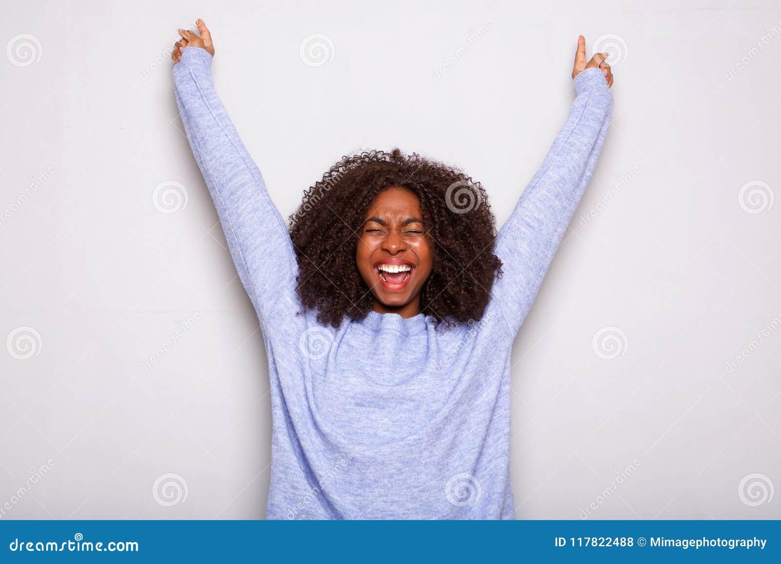欢呼用手的激动的年轻非裔美国人的妇女上升了反对白色背景