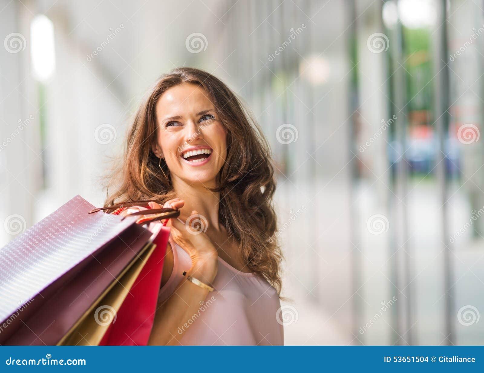 阻止购物袋的棕色毛发,愉快,微笑的妇女