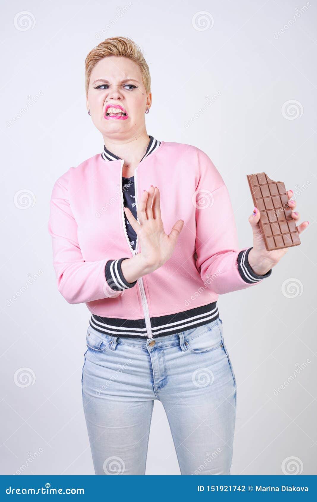正有短的理发立场的大小白种人女孩在有巧克力块的桃红色粗呢夹克在她的手上和展示恨情感f