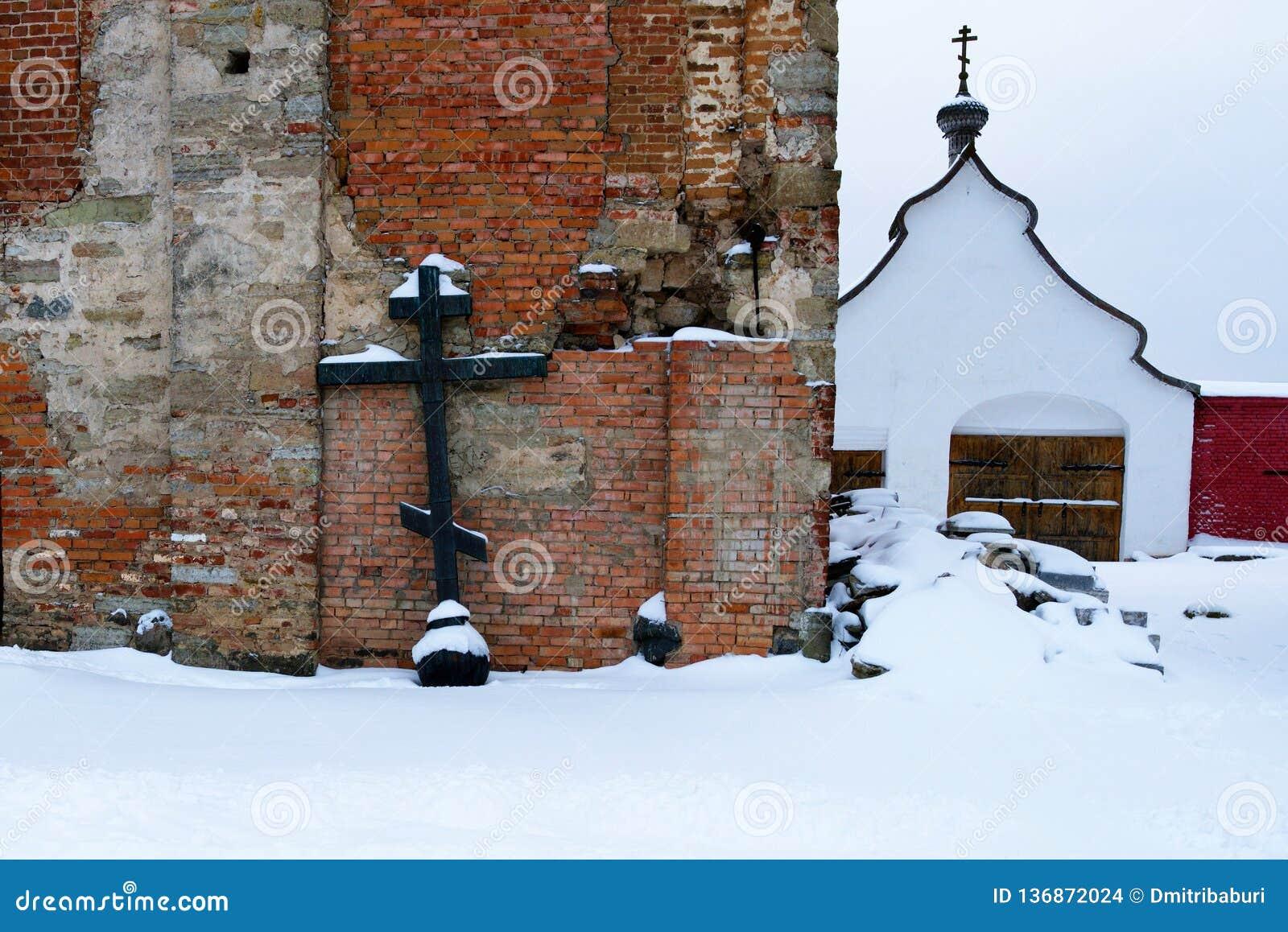 正统十字架,从被毁坏的教堂的圆顶的射击在人的修道院里,俄罗斯,冬天