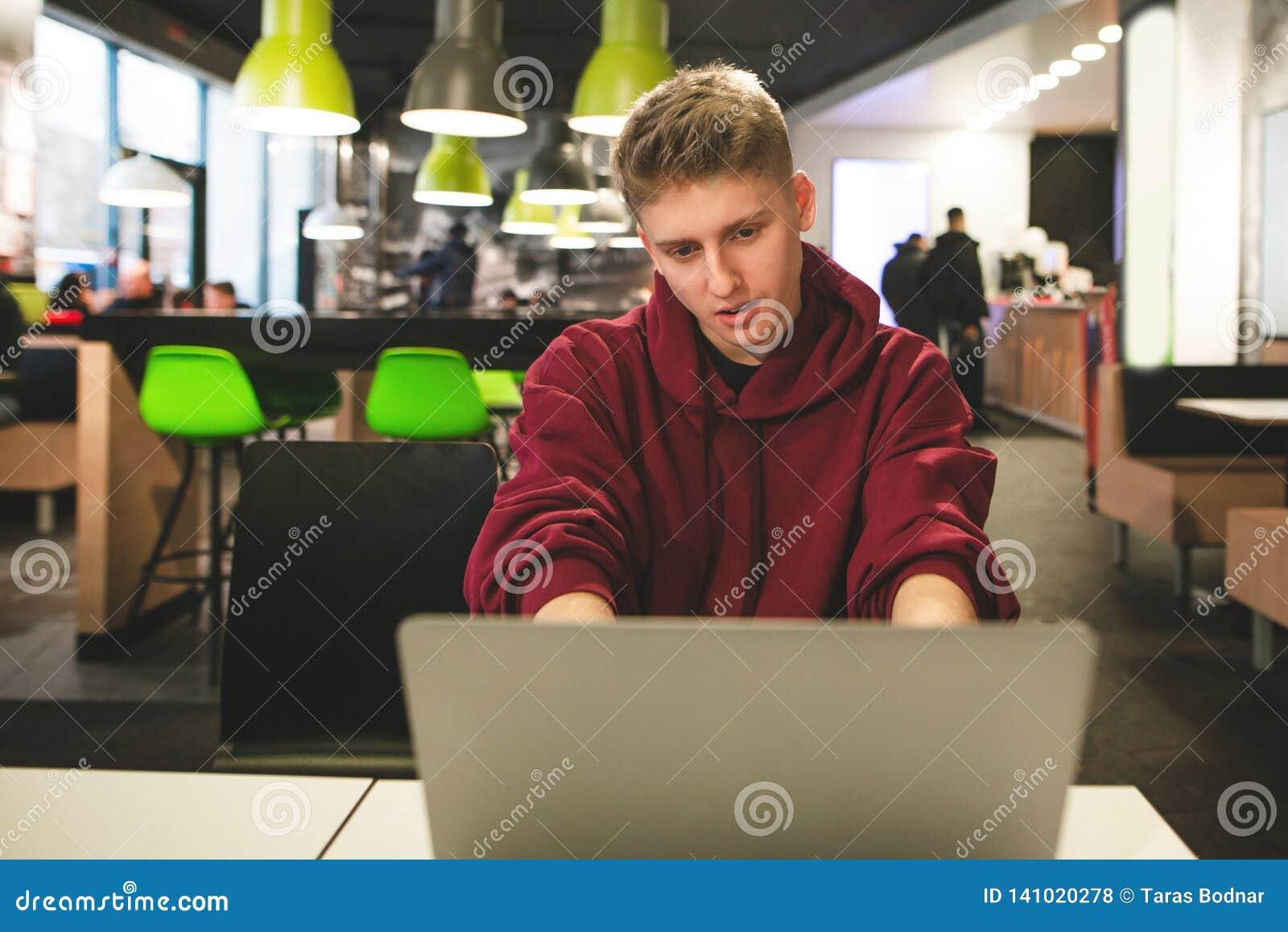 正面人研究在餐馆的背景的一台膝上型计算机 愉快的学生工作