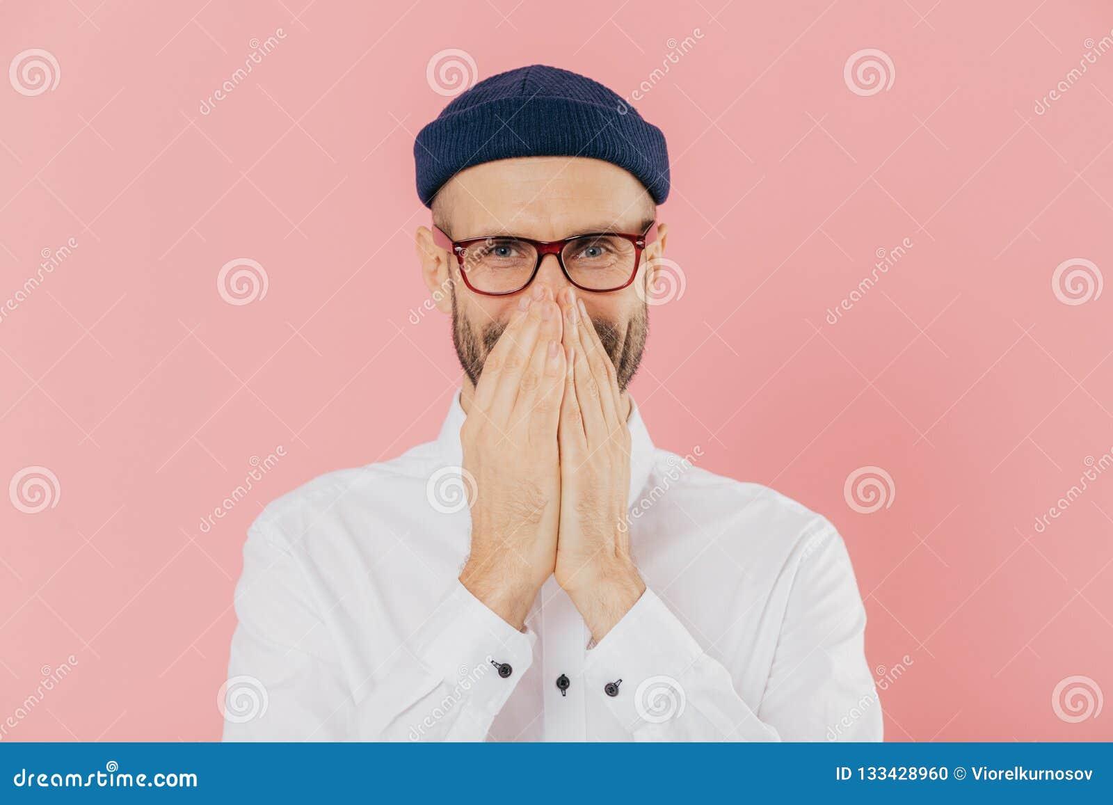 正面高兴的男性水平的射击表现出正面情感,用两只手,嘻嘻笑默默地盖嘴,佩带头饰
