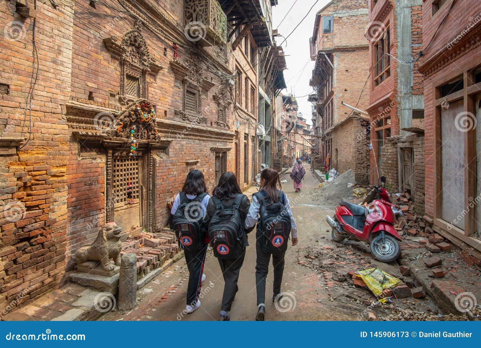 步行沿着向下一条狭窄的街道的三所学校女孩