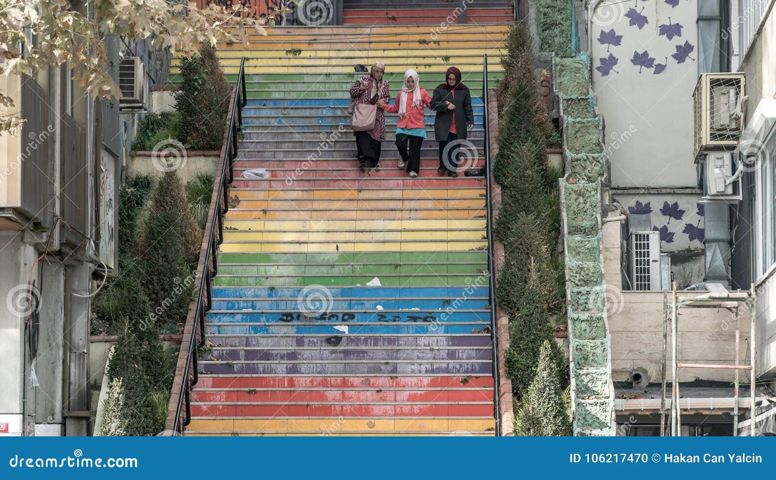 步行沿着向下台阶的3名妇女绘在彩虹颜色在伊斯坦布尔,土耳其