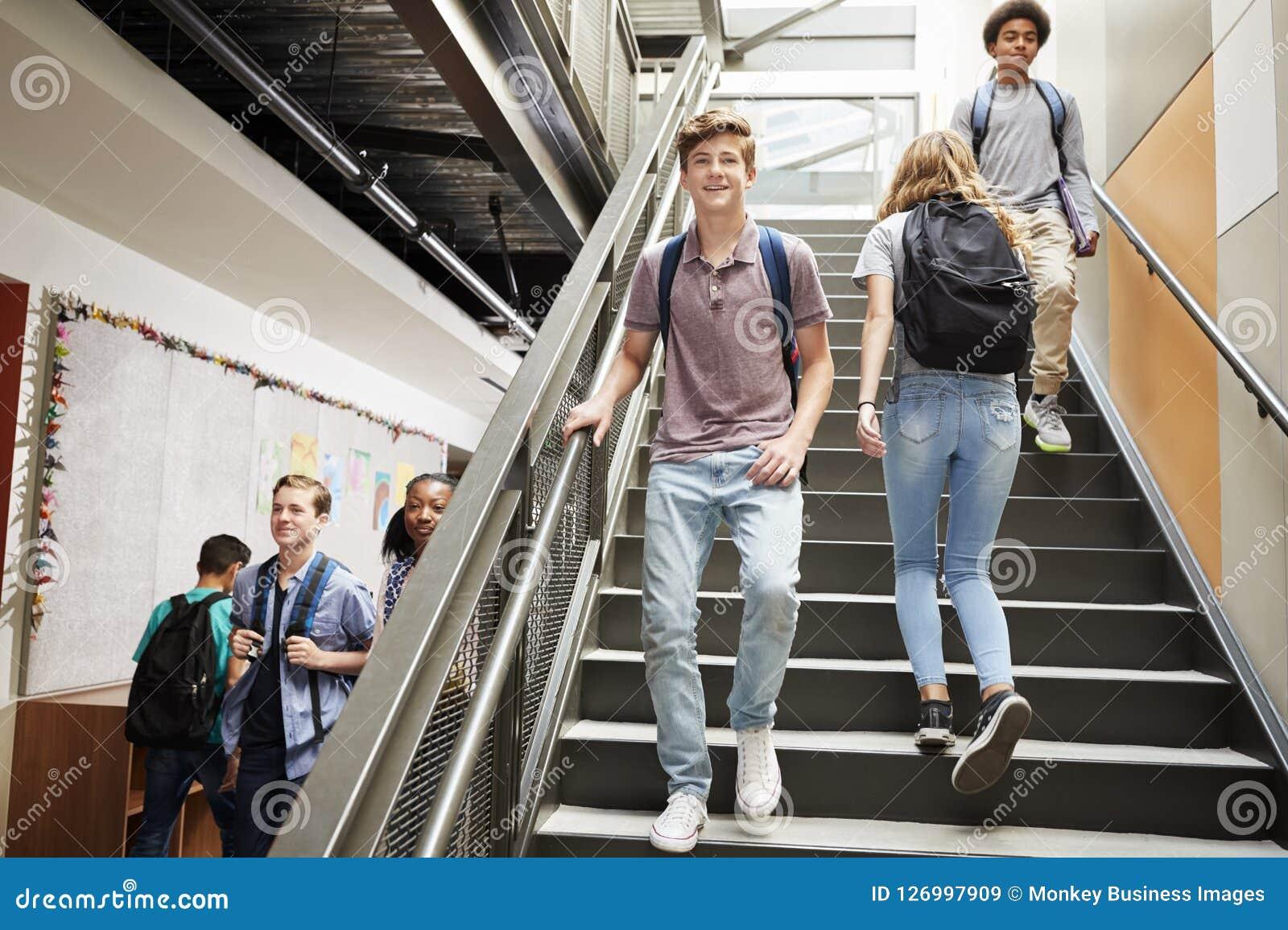 步行沿着向下在繁忙的学院大厦的台阶的高中学生