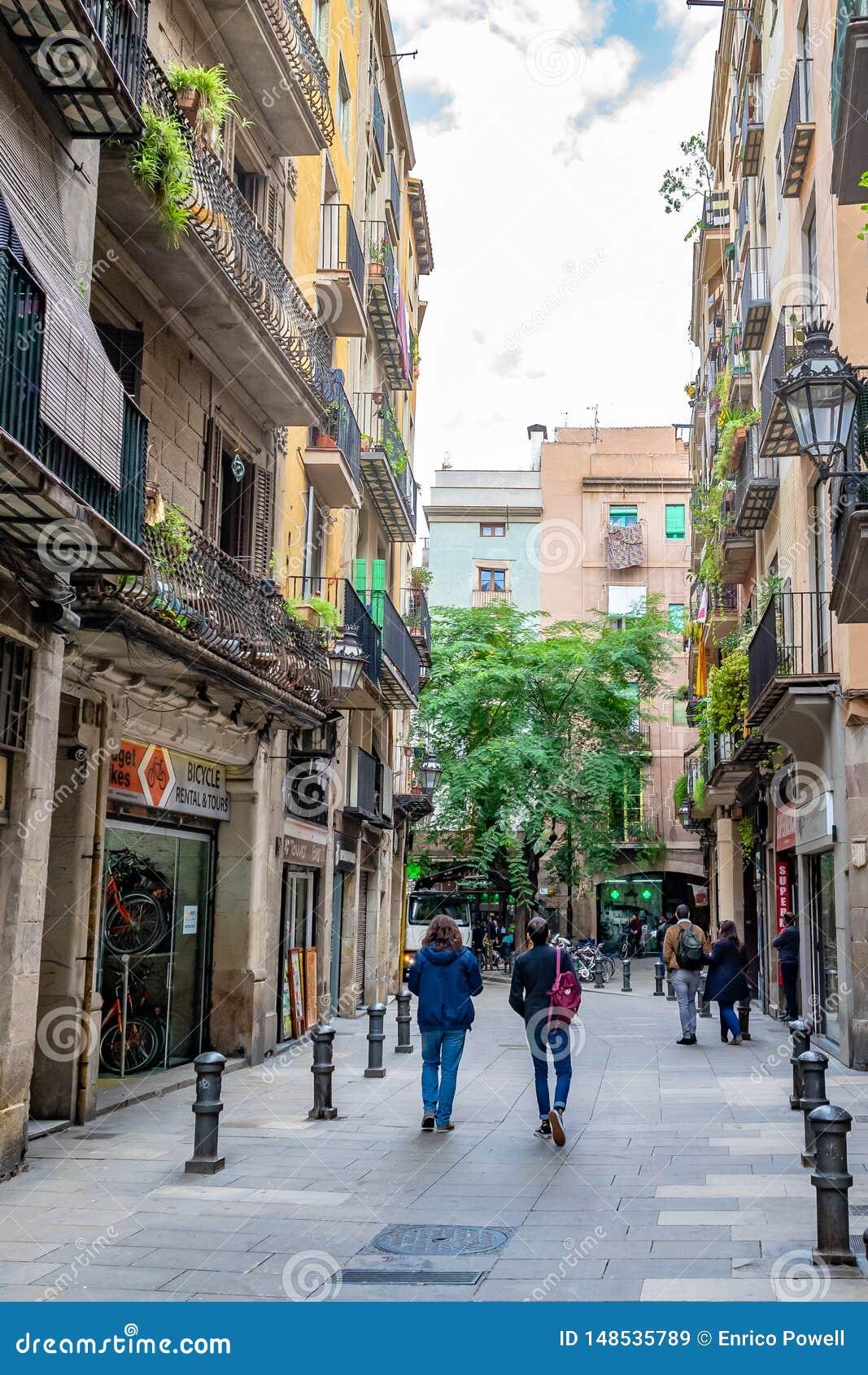 步行沿着向下狭窄的街道的人们在商店/商店之间在巴塞罗那
