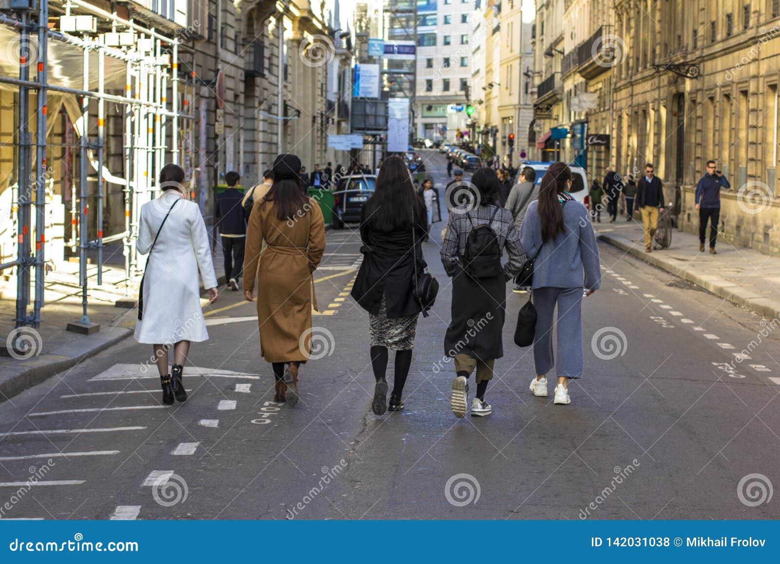 步行沿着向下街道的几个女孩在巴黎,背面图