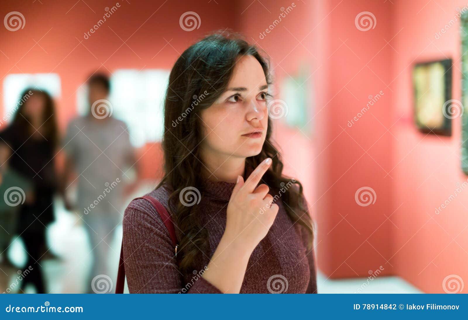 殷勤地看绘画的妇女在美术馆