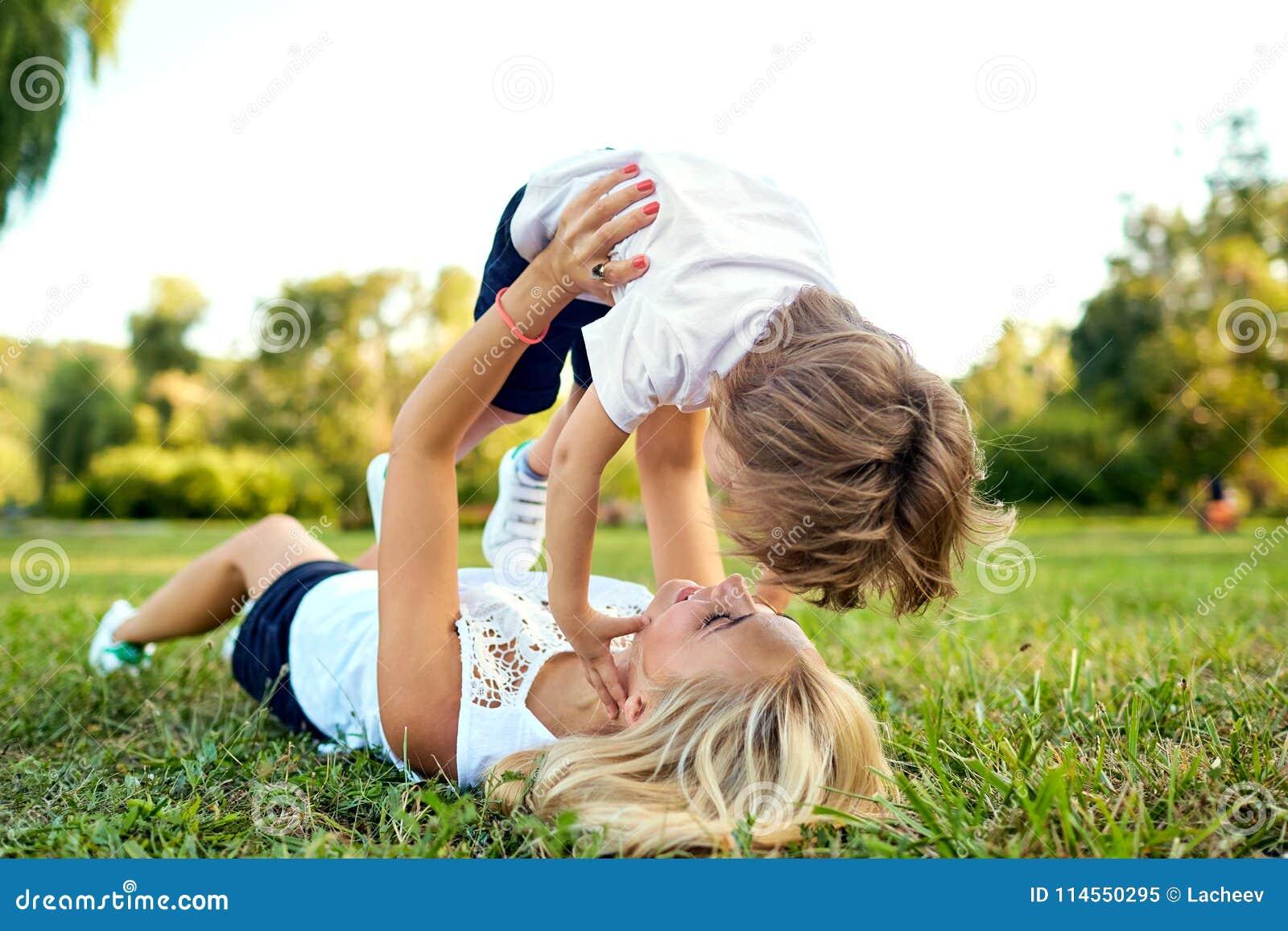 母亲和儿子在公园演奏拥抱在草