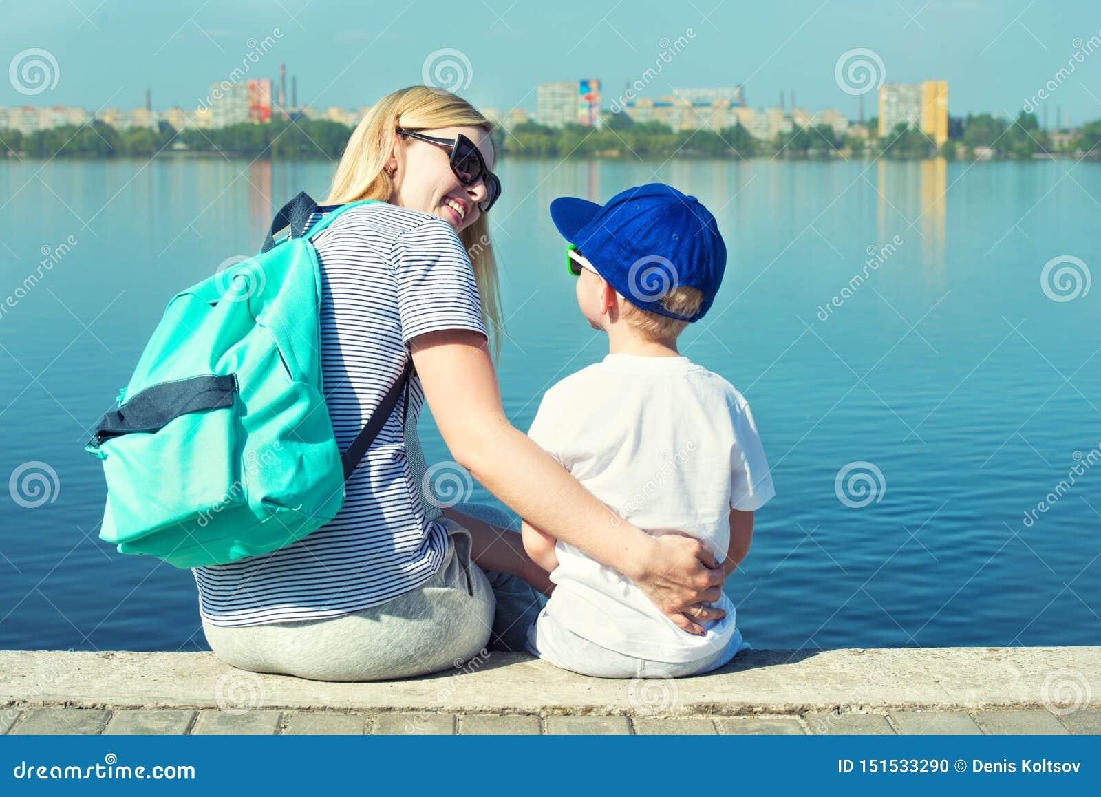 母亲和儿子坐散步和神色在河