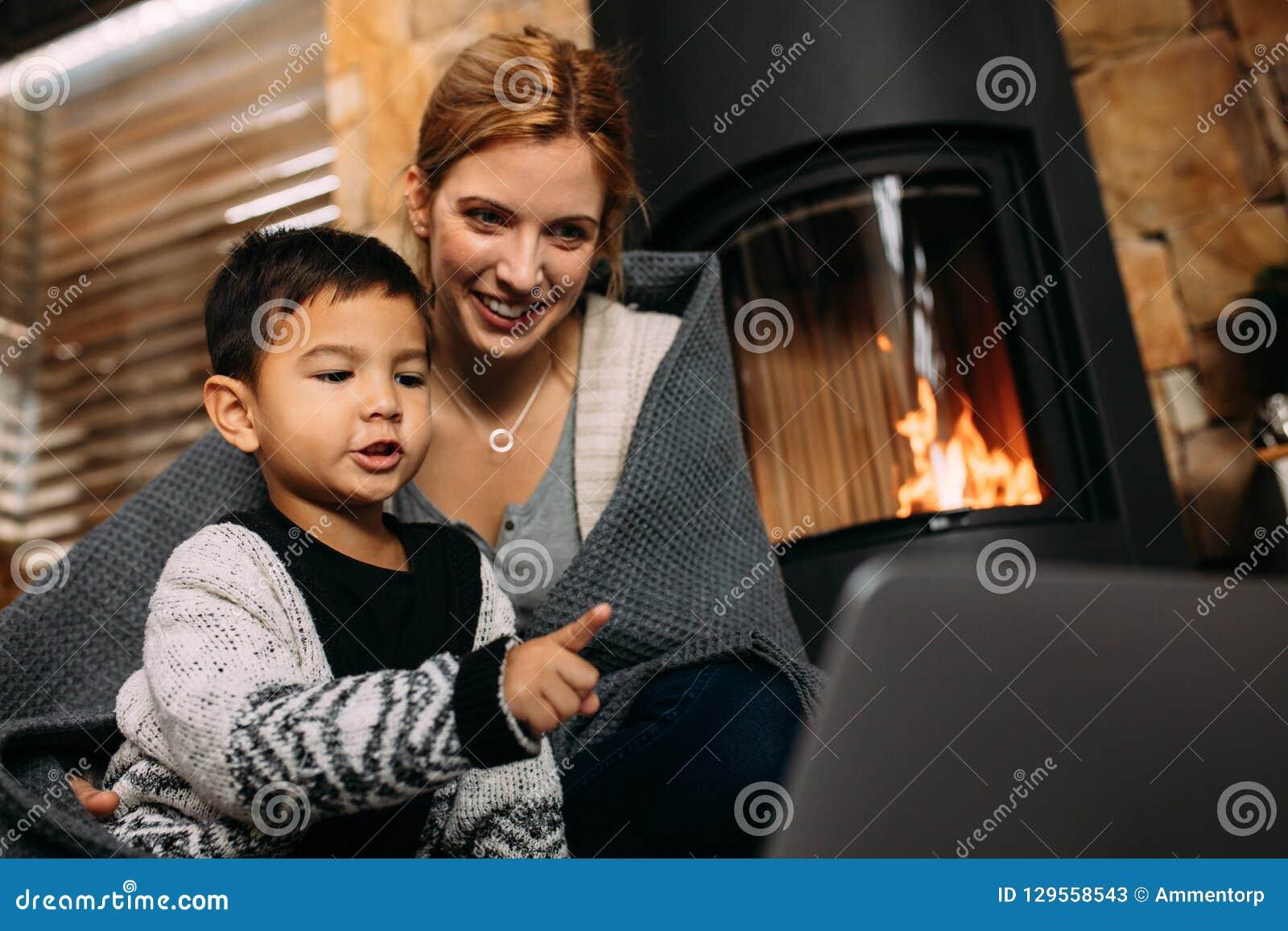 母亲和儿子有膝上型计算机的在家