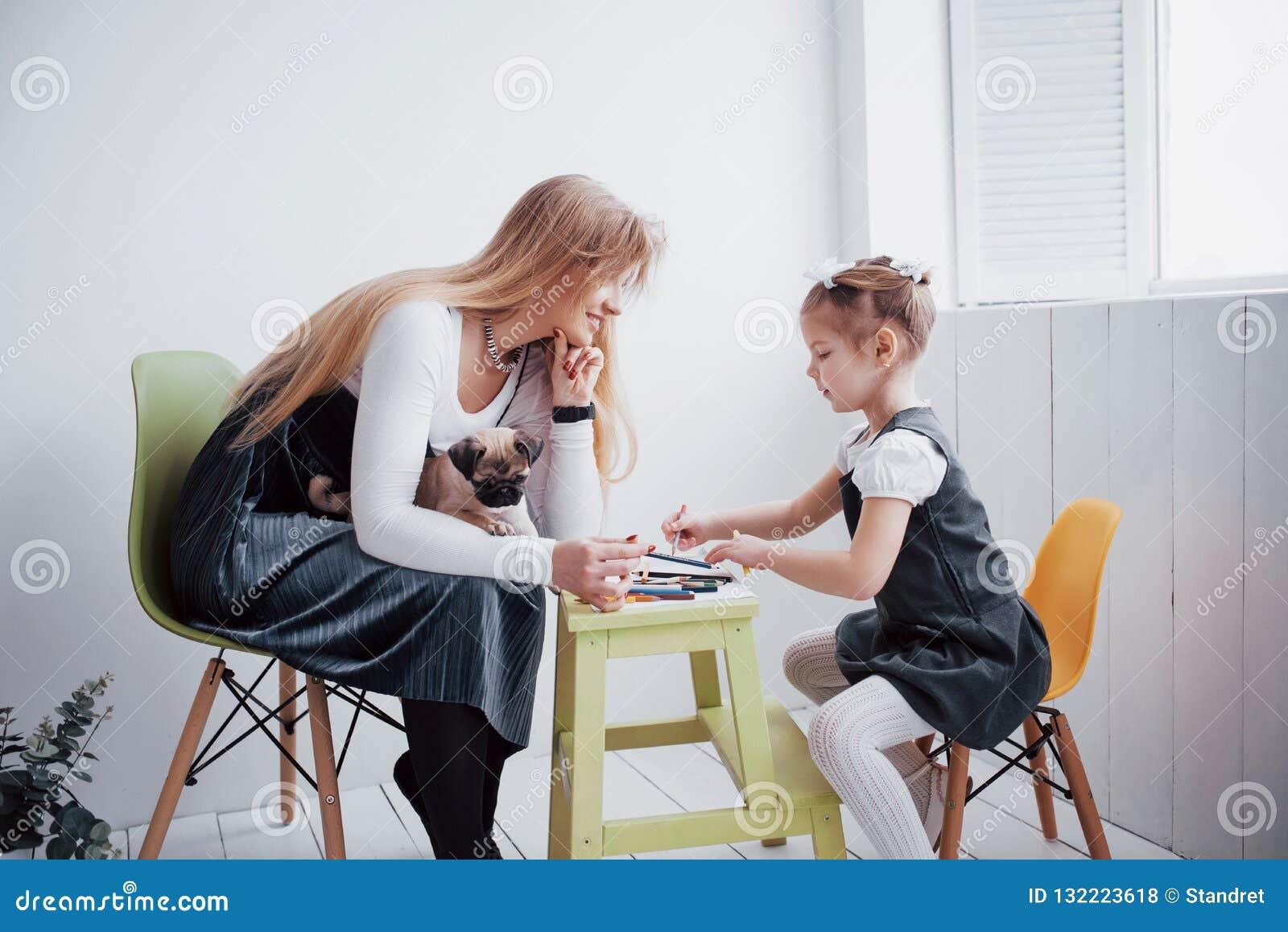 母亲和儿童女儿在幼儿园画参与创造性 与他们的小哈巴狗