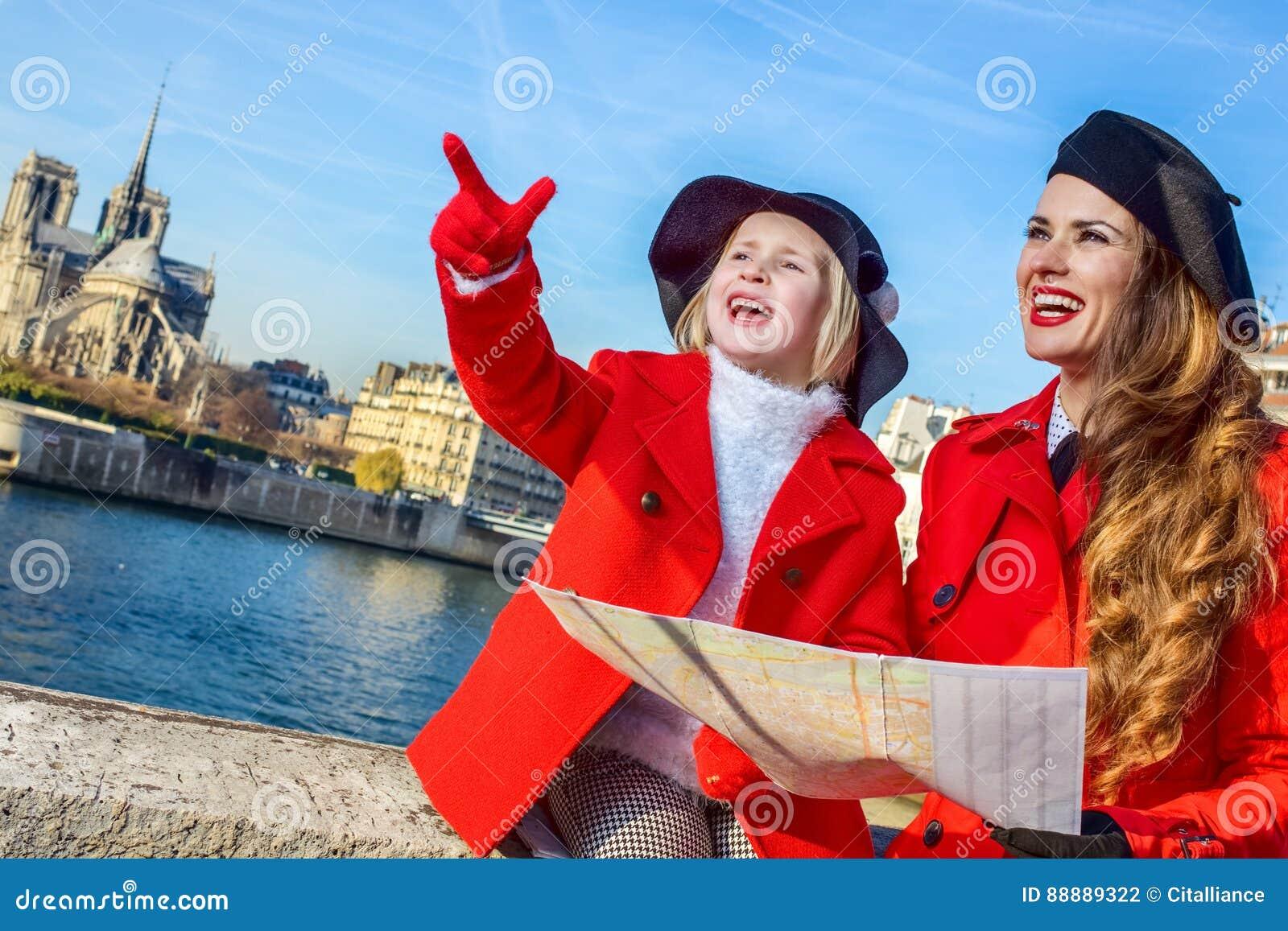 母亲和儿童游人在举行地图和指向的巴黎
