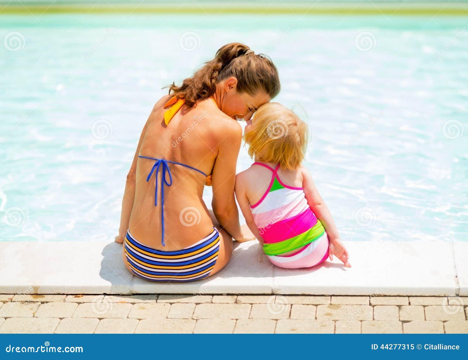 母亲和坐在游泳池附近的女婴
