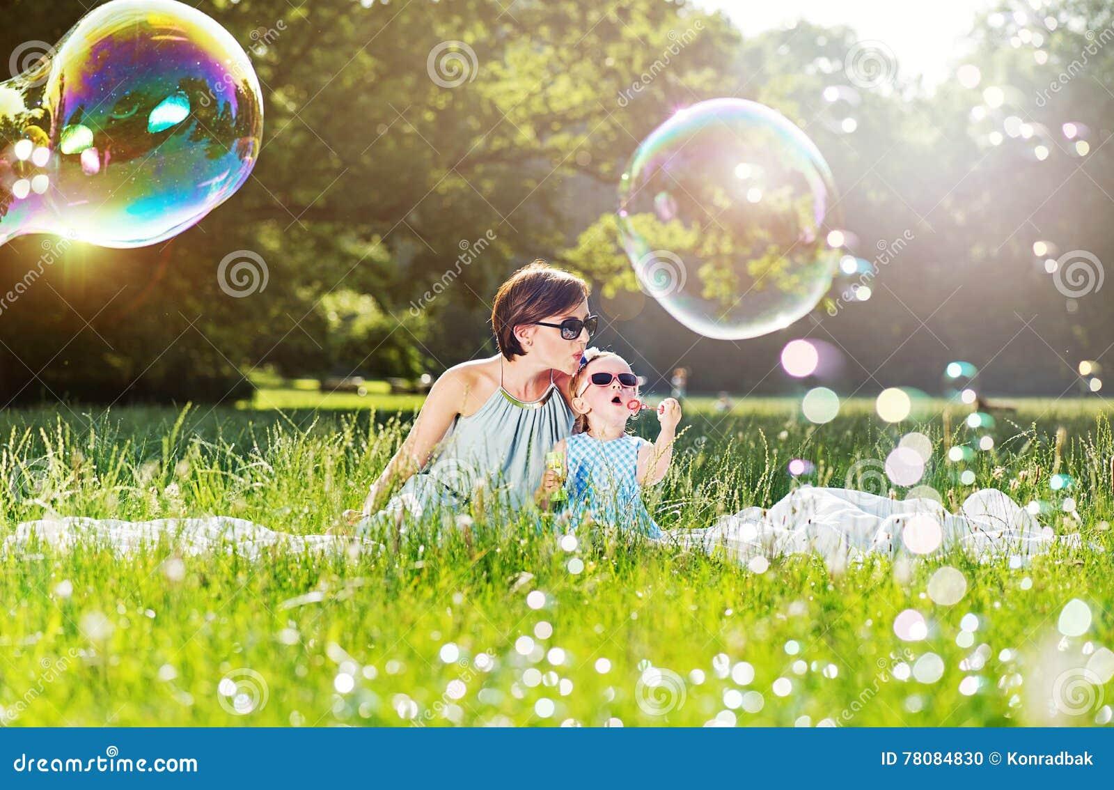 母亲和女儿家庭时间,吹的肥皂泡影