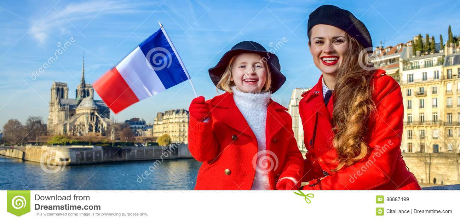 母亲和女儿旅行家在巴黎,显示旗子的法国