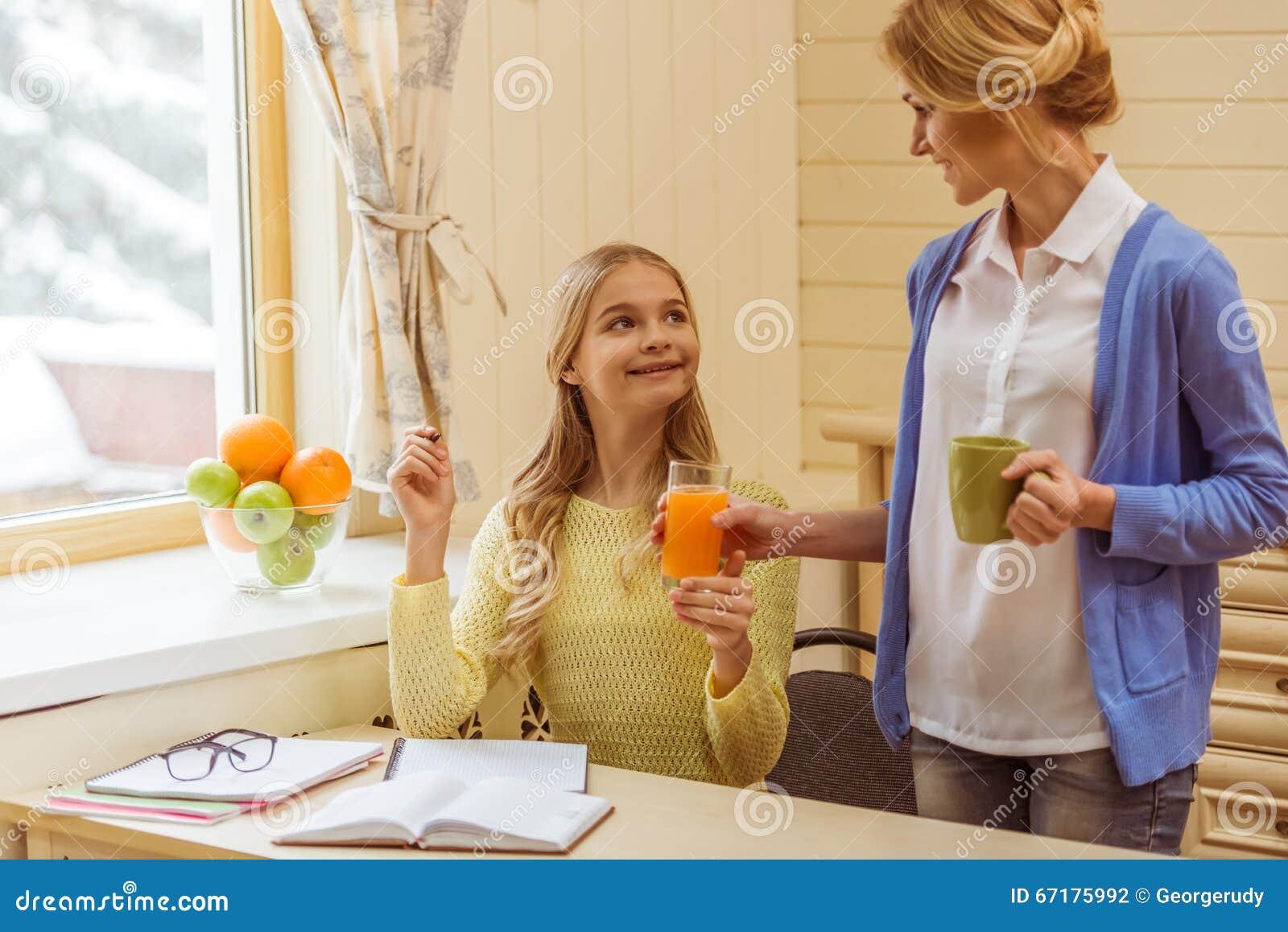 干了女儿和她的两个美丽女同学_做家庭作业,美丽的母亲的可爱的十几岁的女孩拿着杯子和给她的女儿