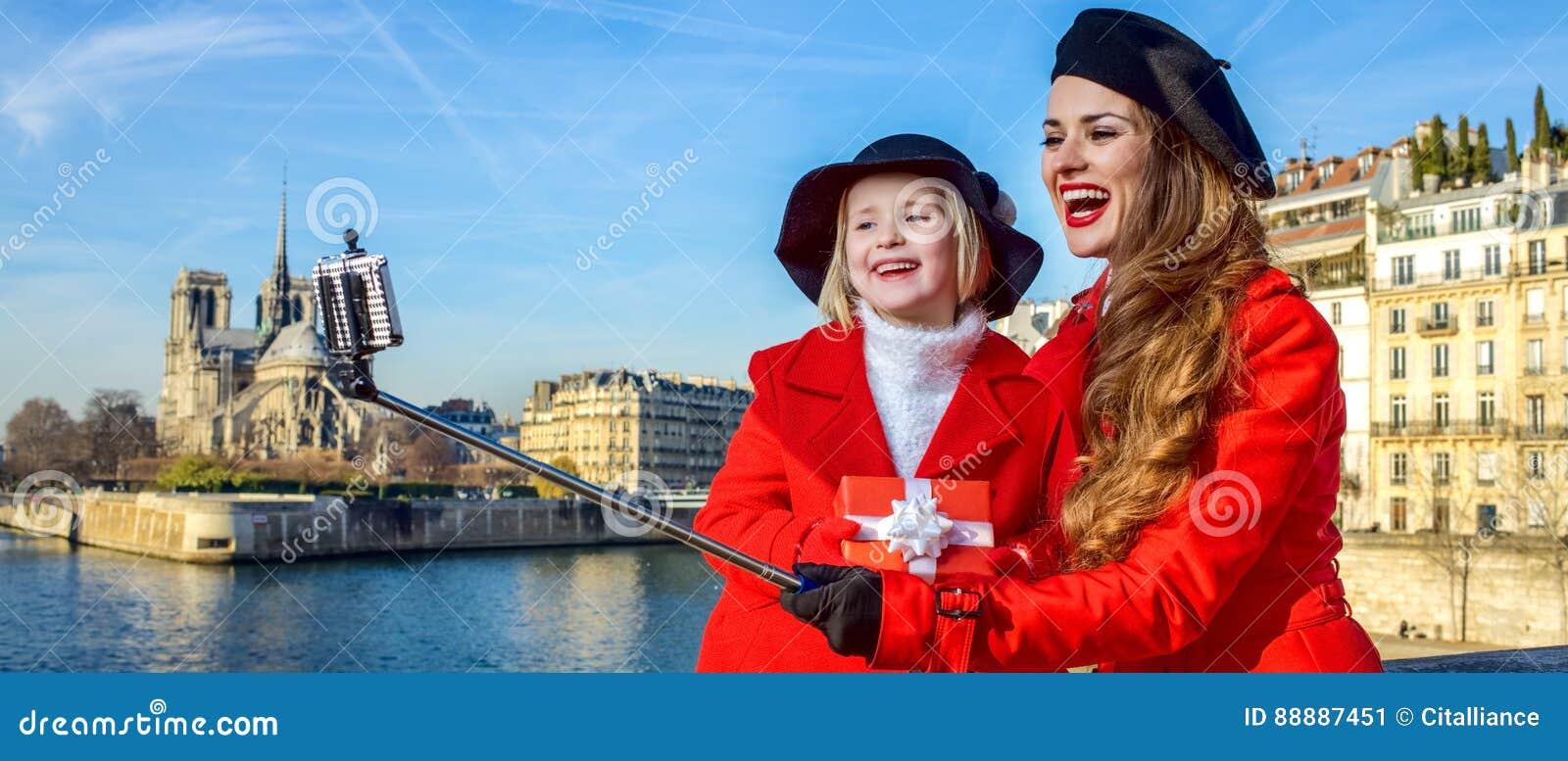 母亲和孩子有圣诞节礼物的把采取selfie装箱,巴黎