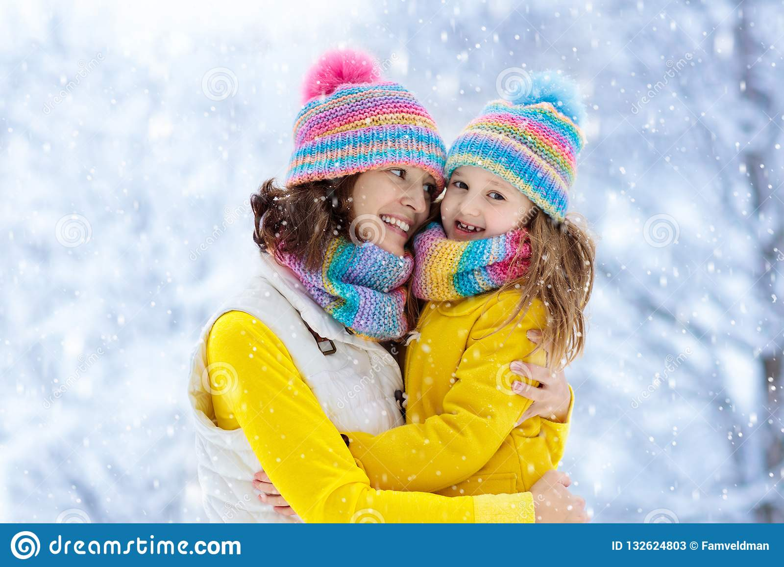 母亲和孩子被编织的冬天帽子的在雪